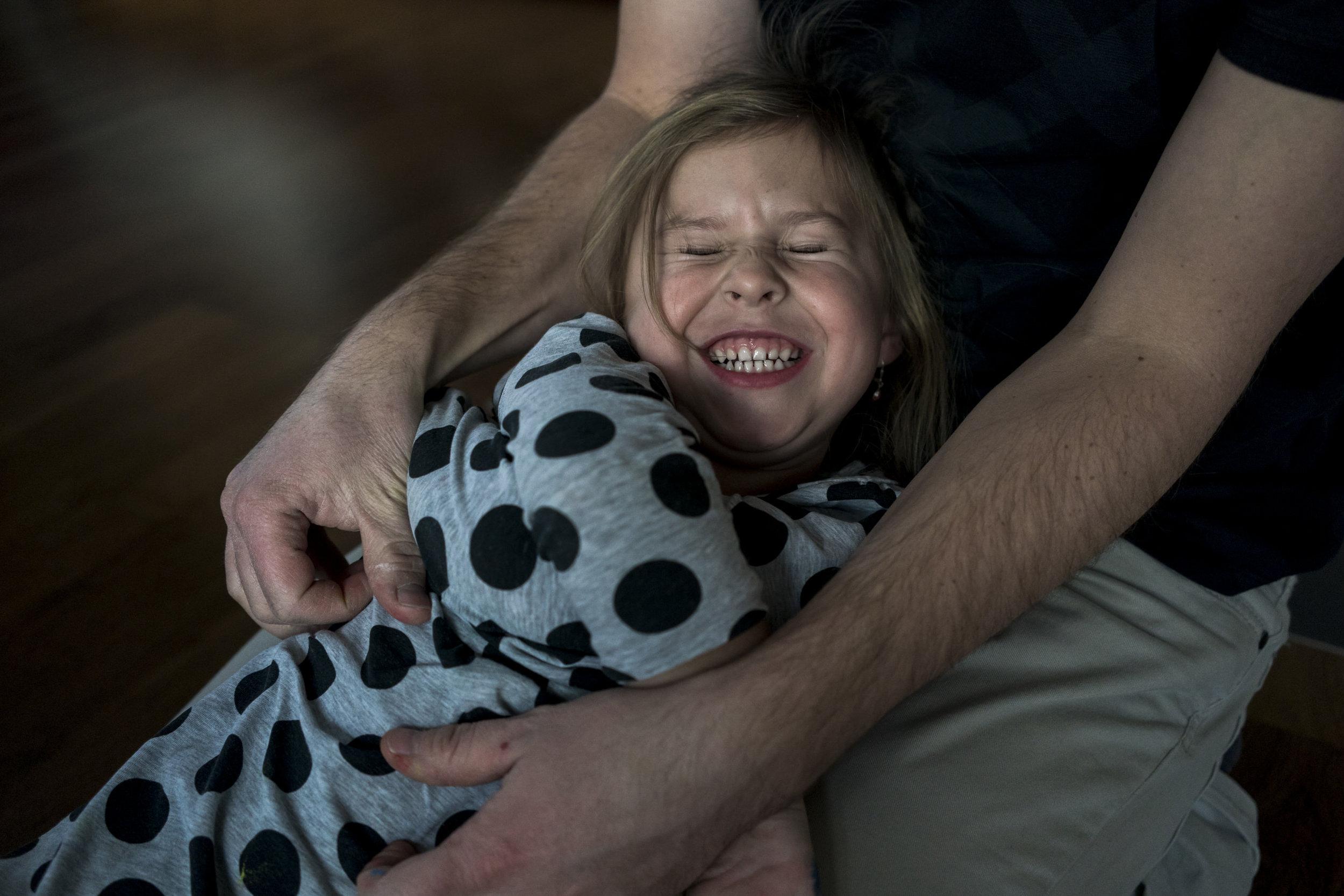 Eines meiner liebsten Familienfotos - lachendes Mädchen, das von ihrem Papa gekitzelt wird