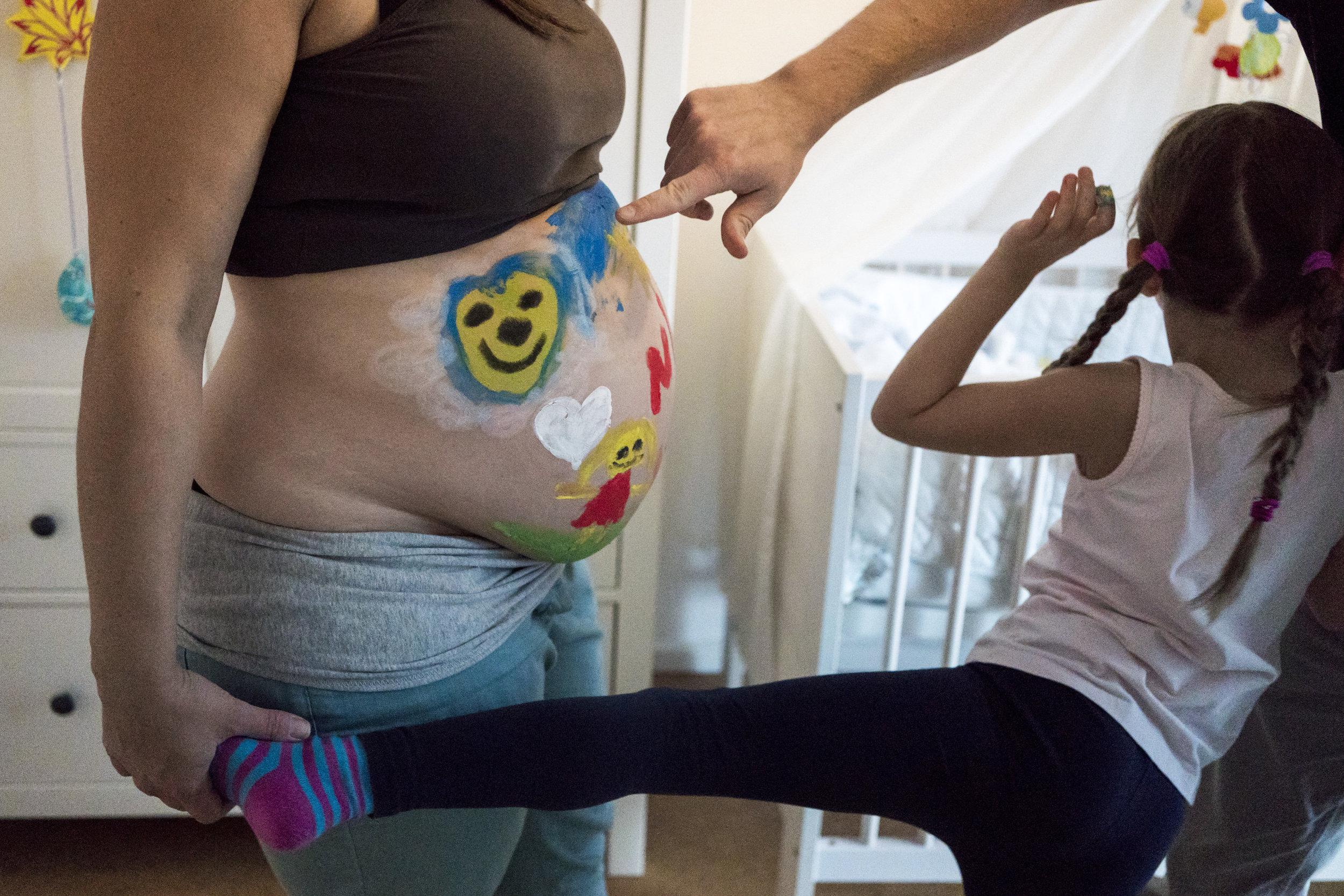 Eines meiner liebsten Babybauchfotos aus einer Familienreportage - Papa zeigt auf den schwangeren Bauch seiner Frau