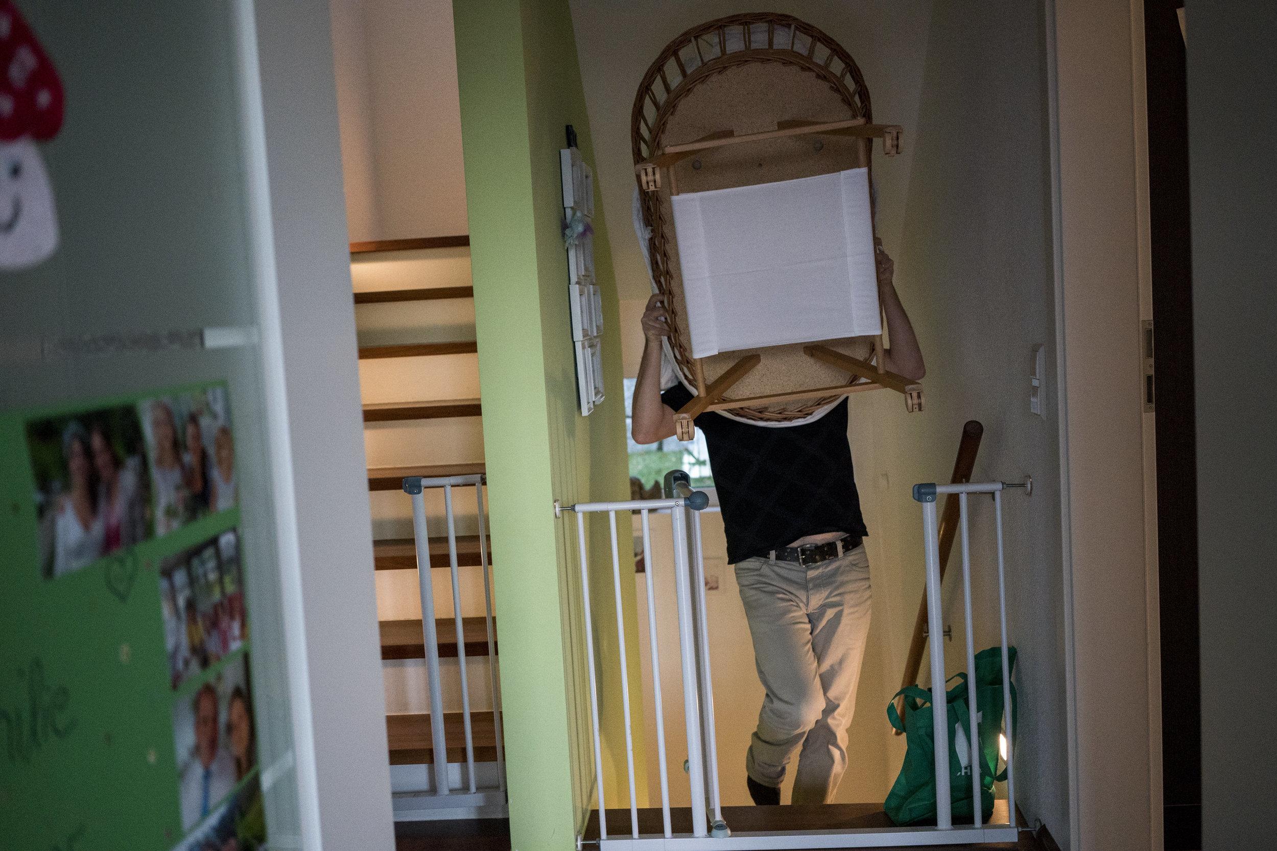 Eines meiner liebsten Familienfotos aus einer Familienreportage - Papa trägt den Stubenwagen auf dem Kopf ins Wohnzimmer