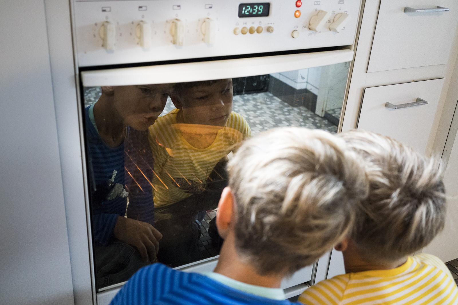 Jungen vor Herd in Küche | Familienfotografin unterwegs - Familienfotos drinnen und draussen