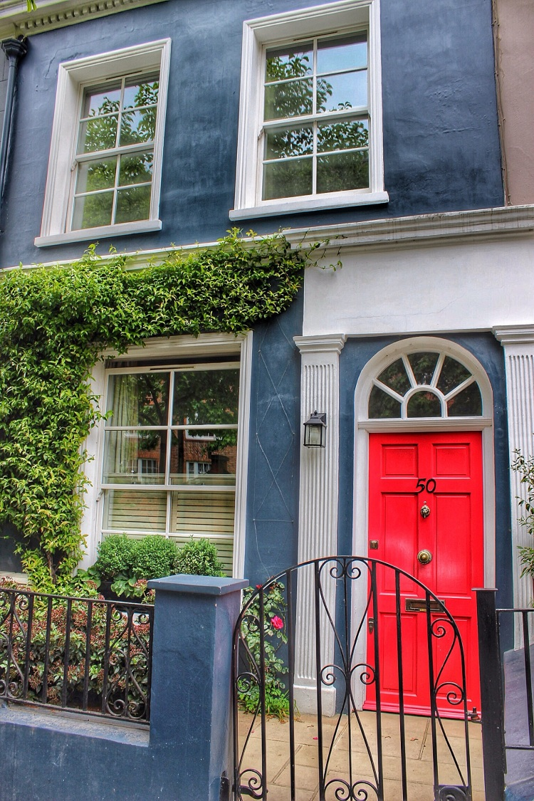 Vibrant red front door with a contrasting choice of blue render. Strong and bold.