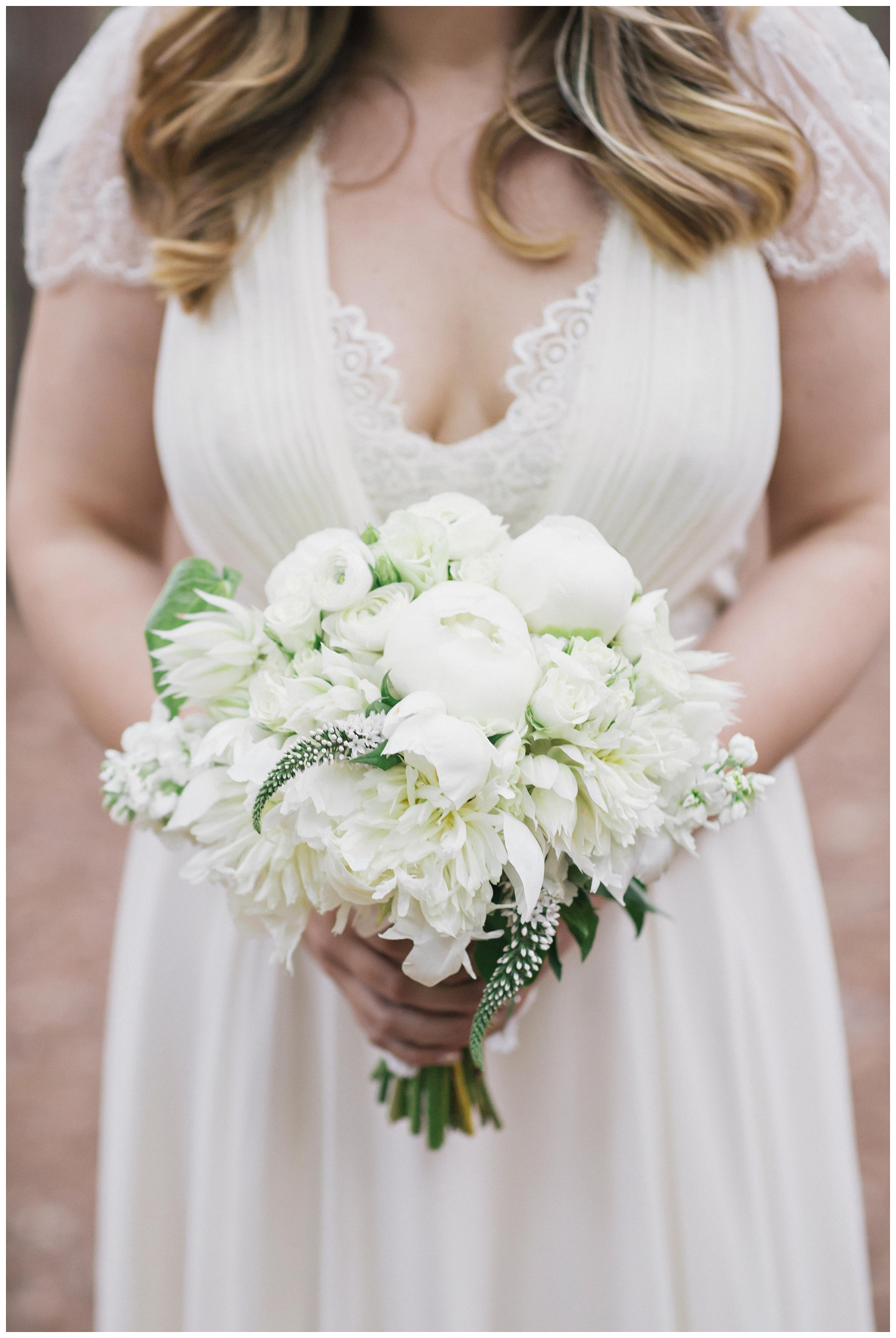 The Roxbury Barn Wedding Venue | Bride holding white flowers | Barn Wedding