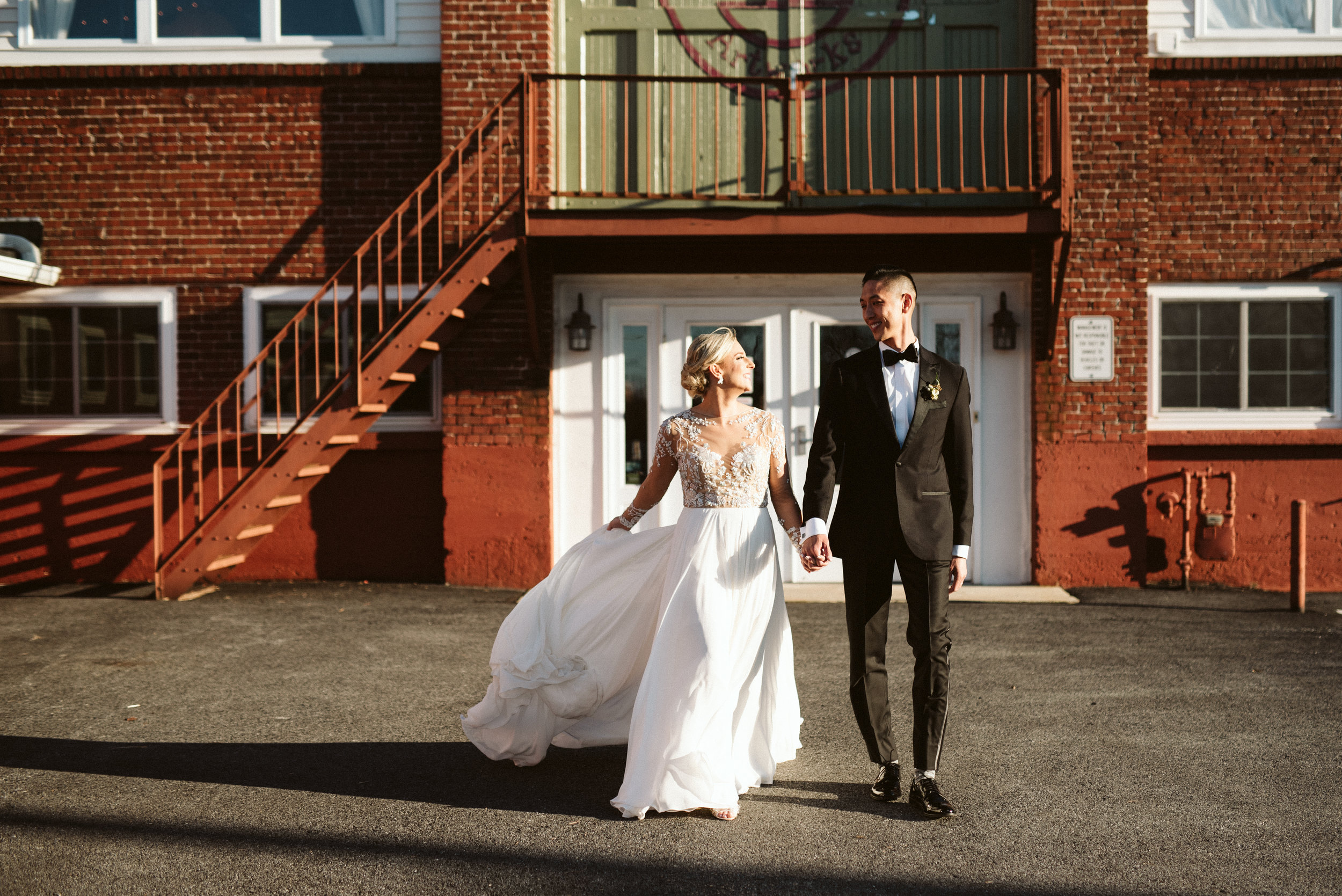 SUBJECT: The image above is a photograph of a beautiful bride with blue eyes and blonde hair, wearing a beaded, flowy white wedding dress. The groom is Chinese and is wearing a black tux.  ARTIST: The photographer is Alyssa Christine Photography, who is based in Lancaster, Pennsylvania and the image was captured at the wedding location of The Reading Art Works.  DETAILS: The wedding dress designer is Hayley Paige.