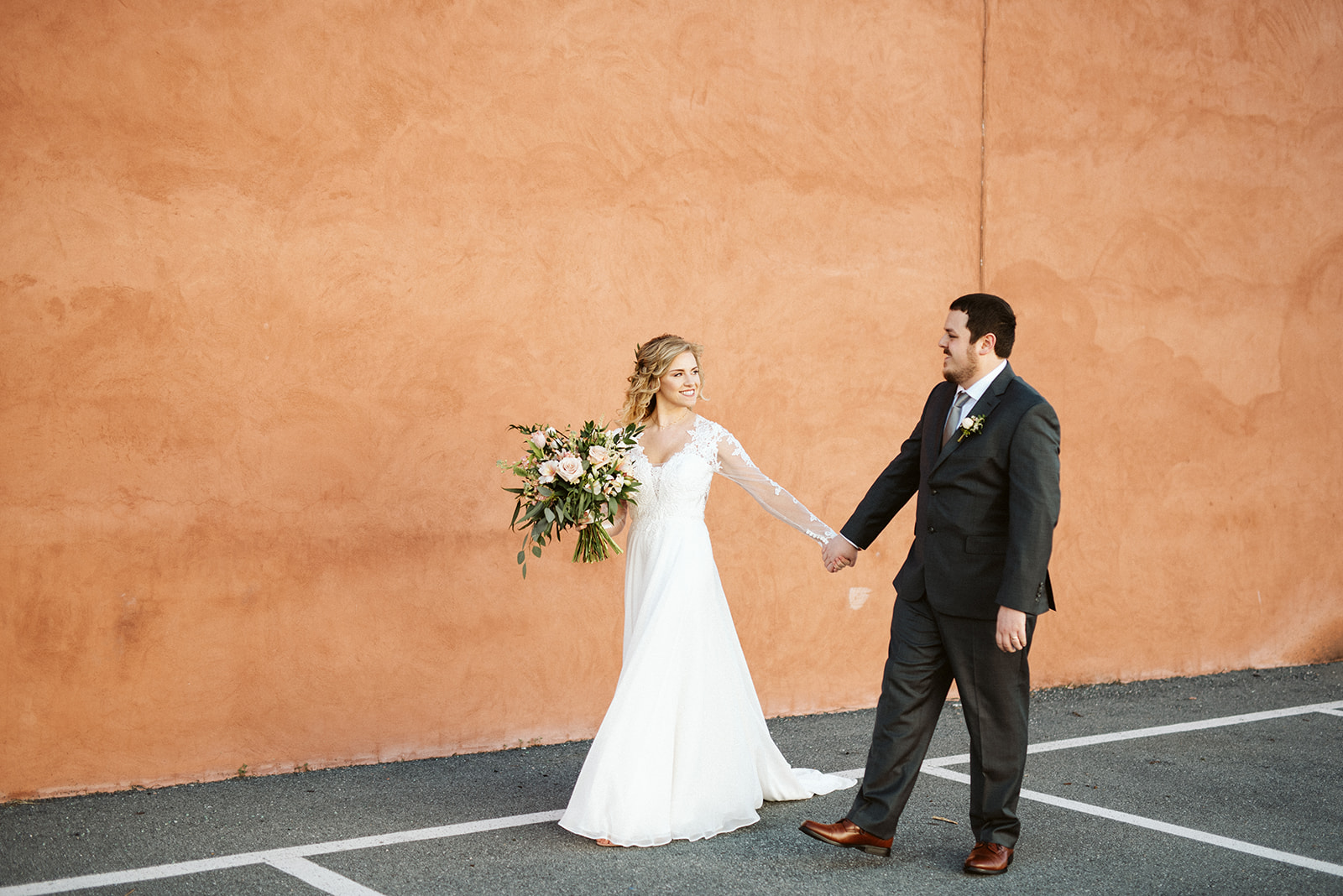 Cork Factory Hotel, Lancaster, PA Wedding - Bride and Groom walking past the peach wall on the exterior of the Cork Factory Hotel property.