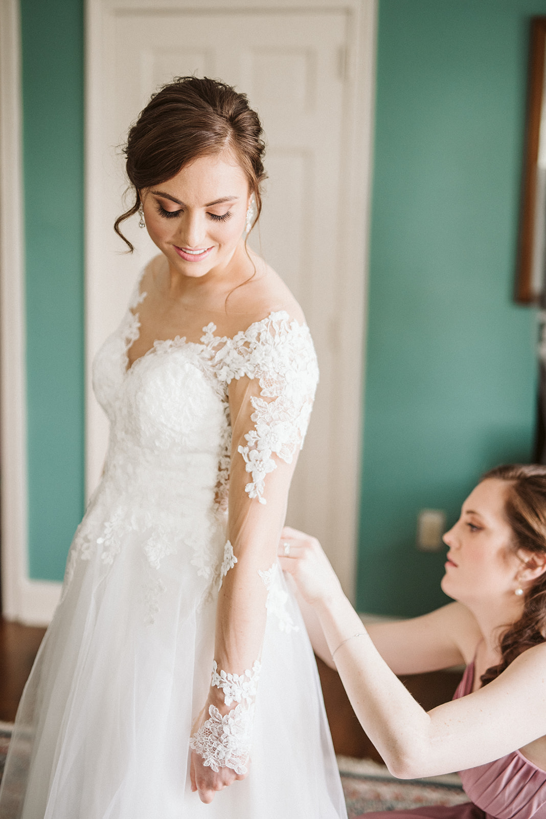 Bride getting into her dress within the bridal suite of Drumore Estate located in Pequea, Pennsylvania.