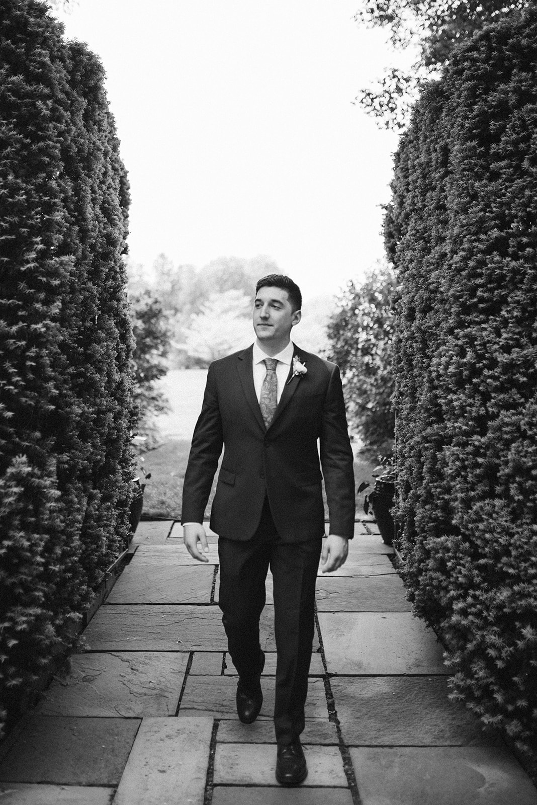 A groom walks to his First Look on the estate grounds at Drumore Estate.