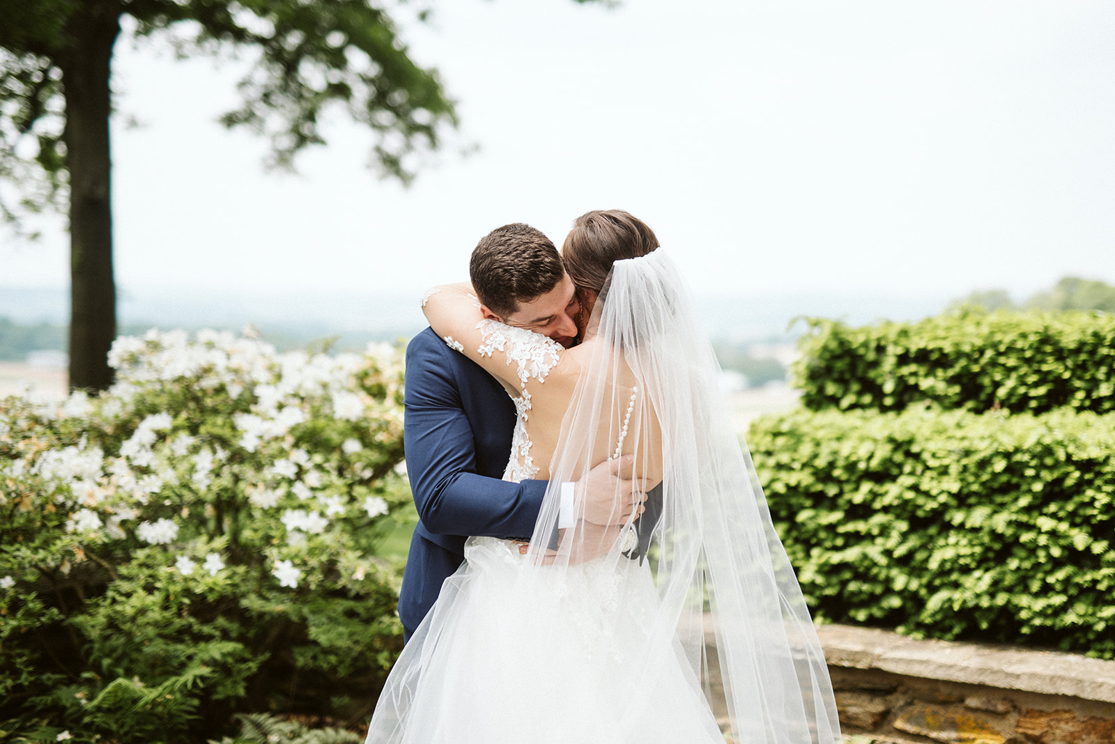 Bride and groom embrace during their first look overlooking southern Lancaster County from Drumore Estate.
