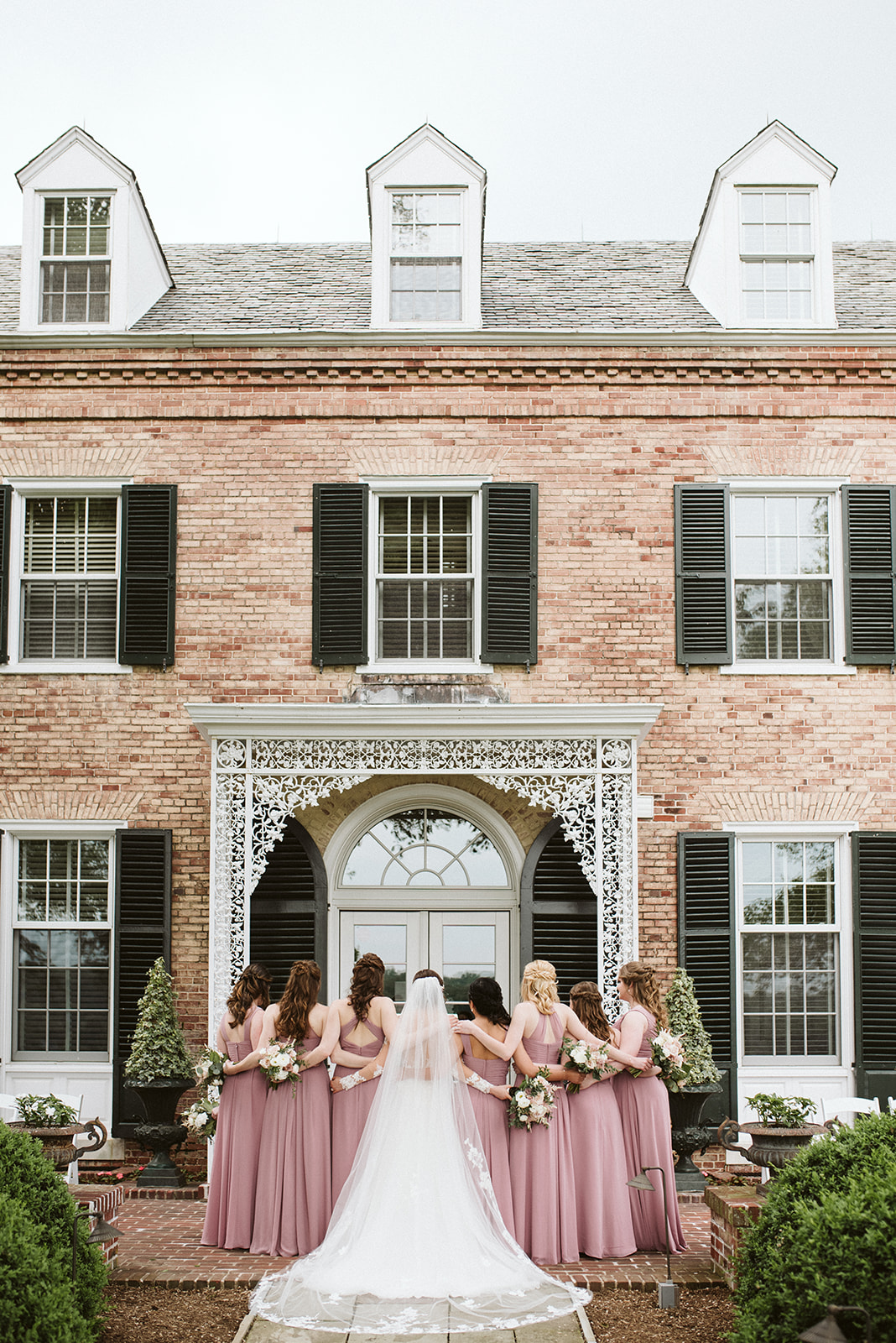 Mauve bridesmaids dresses standing in front of the mansion at Drumore Estate.