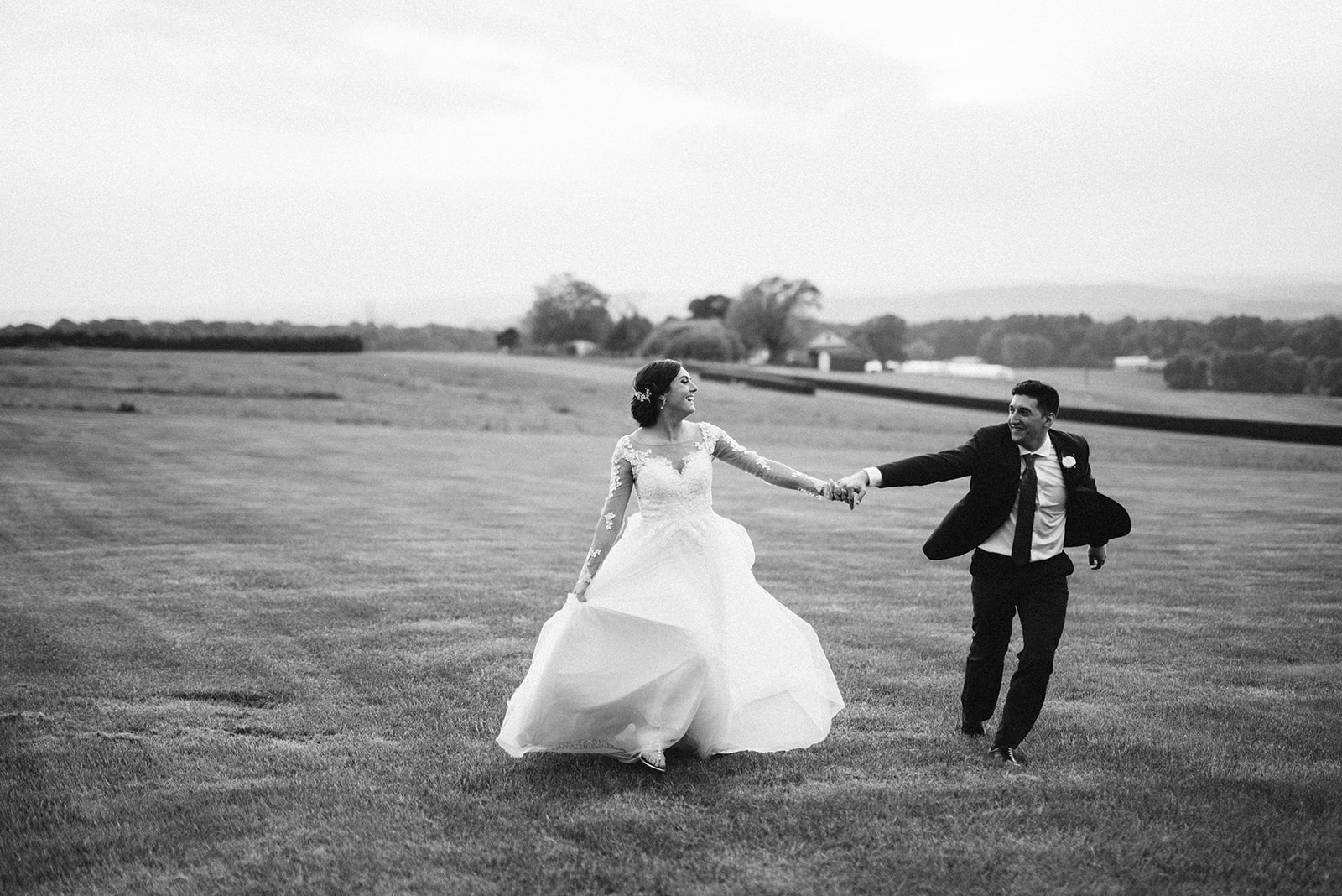 A bride and groom run through a field during their wedding at Drumore Estate.