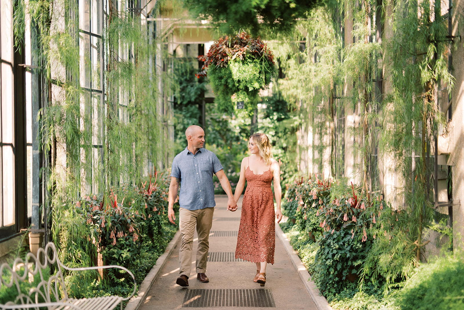 A couple walks through the conservatory at Longwood Gardens during their engagement session.