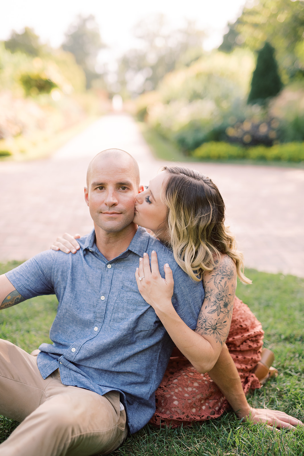 Jasmine kisses Joel's cheek during their engagement session at Longwood Gardens.