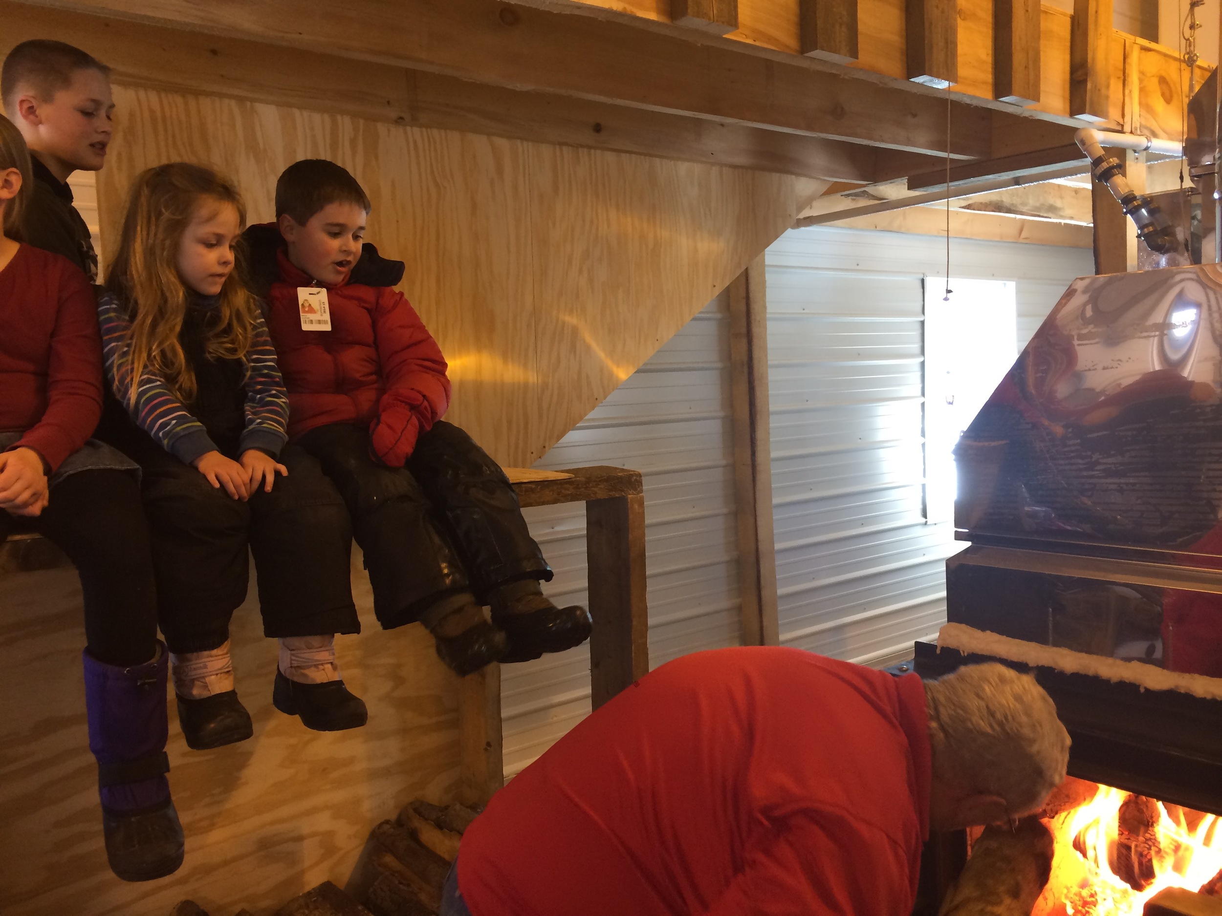 Grandchildren look on from a safe vantage point as Grandad fills the firebox of the evaporator.
