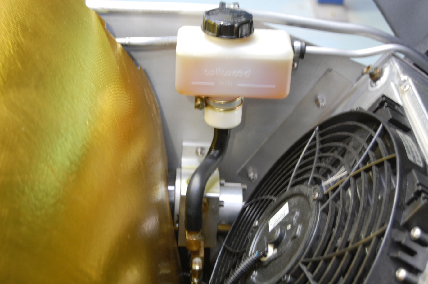 Detail of lift kit pump and reservoir installed in front radiator compartment on a Superlite SL-C.