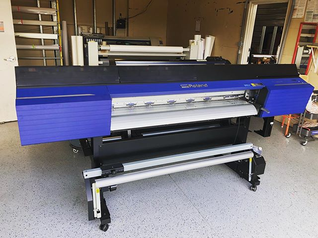 "Exciting day here at the Dog. We welcomed printer number 3. We have all @rolanddga printers in our shop. There's ""Tank"" (SP-540V), ""Frank"" (VS-640i) and now ""Mr Freeze"" (VG2-540) named after Arnold Schwarzenegger. This big blue beast reminded us of muscles, which led to Arnold, which led to Mr Freeze 🥶 from Batman when he played that role. Mr. Freeze will be pumping out all future #wraps mostly and digital media signage for all our fantastic clients. #iceiceice"