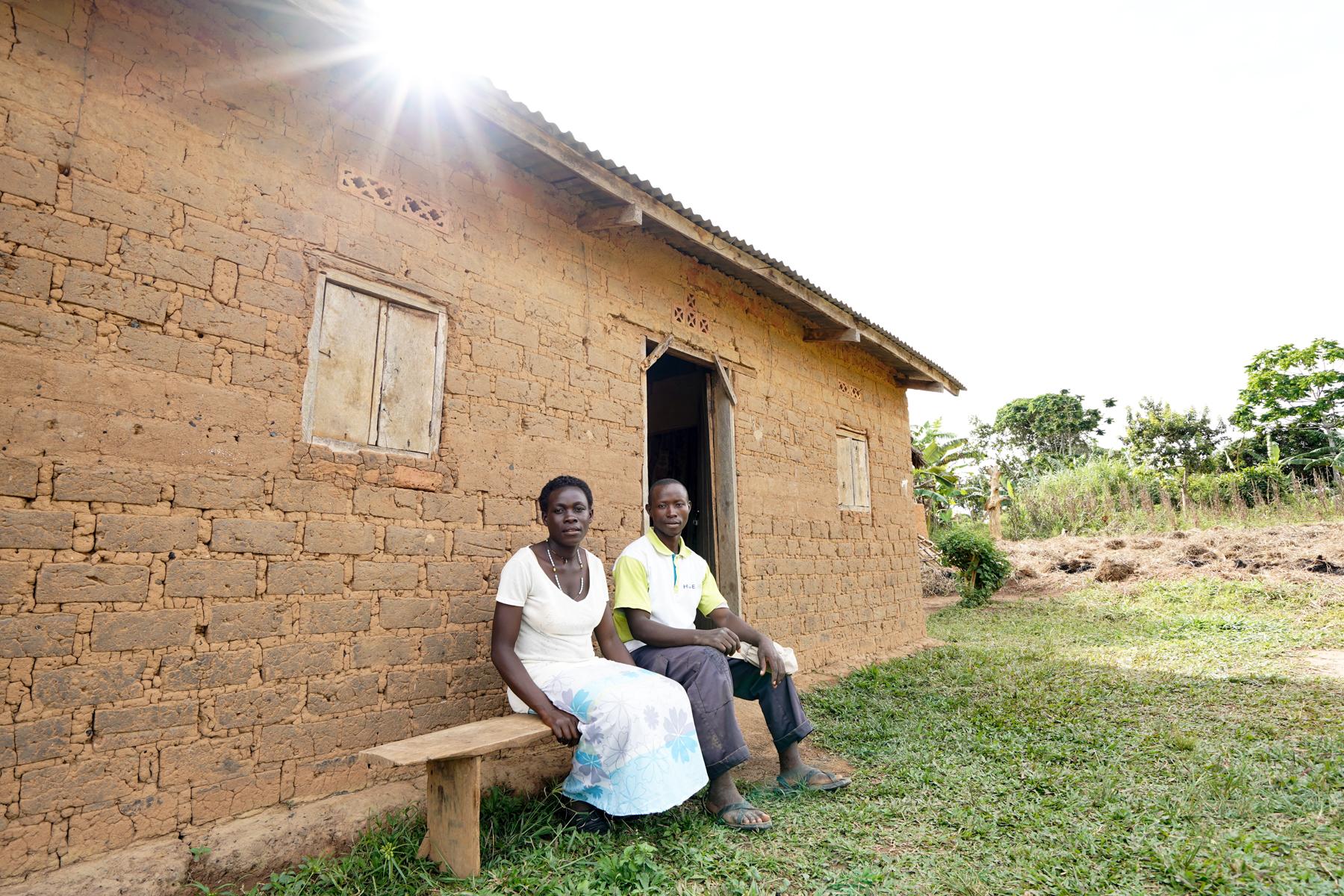 A couple sits outside their home on Zinga Island, Uganda