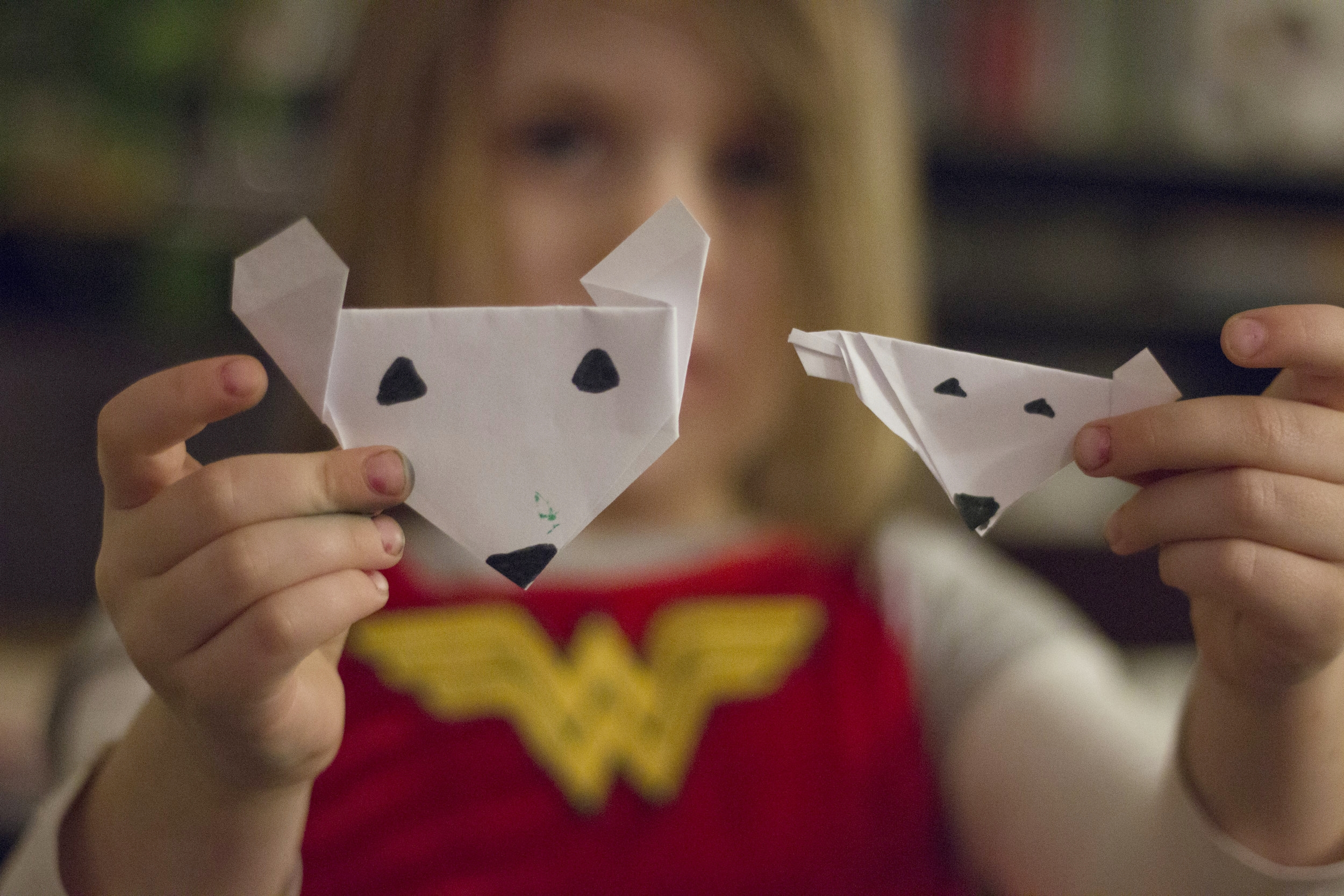 Shiloh holds up two paper foxes she made.