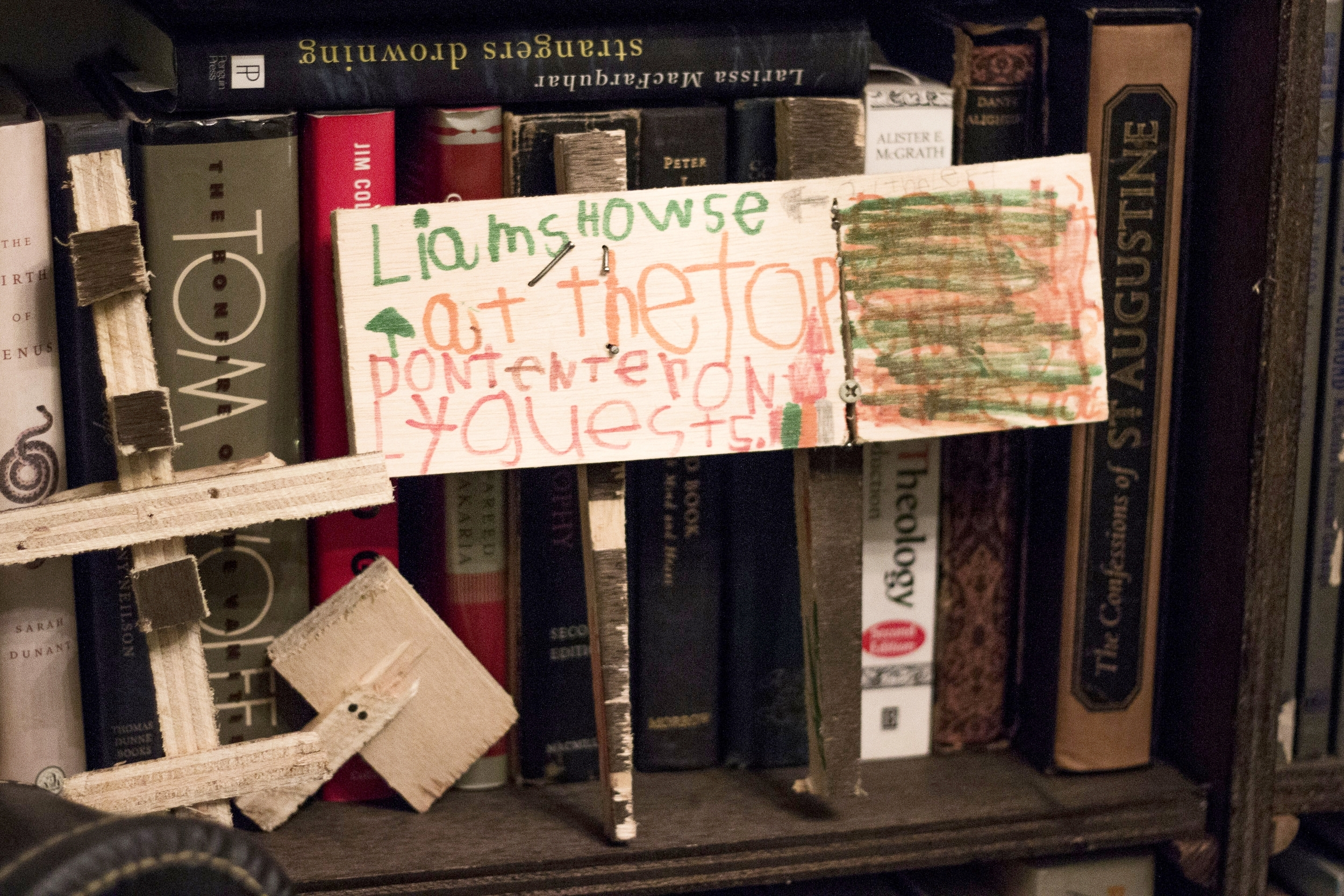 "Liam's sign, which reads ""Liam's howse at the top don't enter only guests,"" rests on Kiranne's bookshelf. The bookshelf occupies almost an entire wall of their apartment."