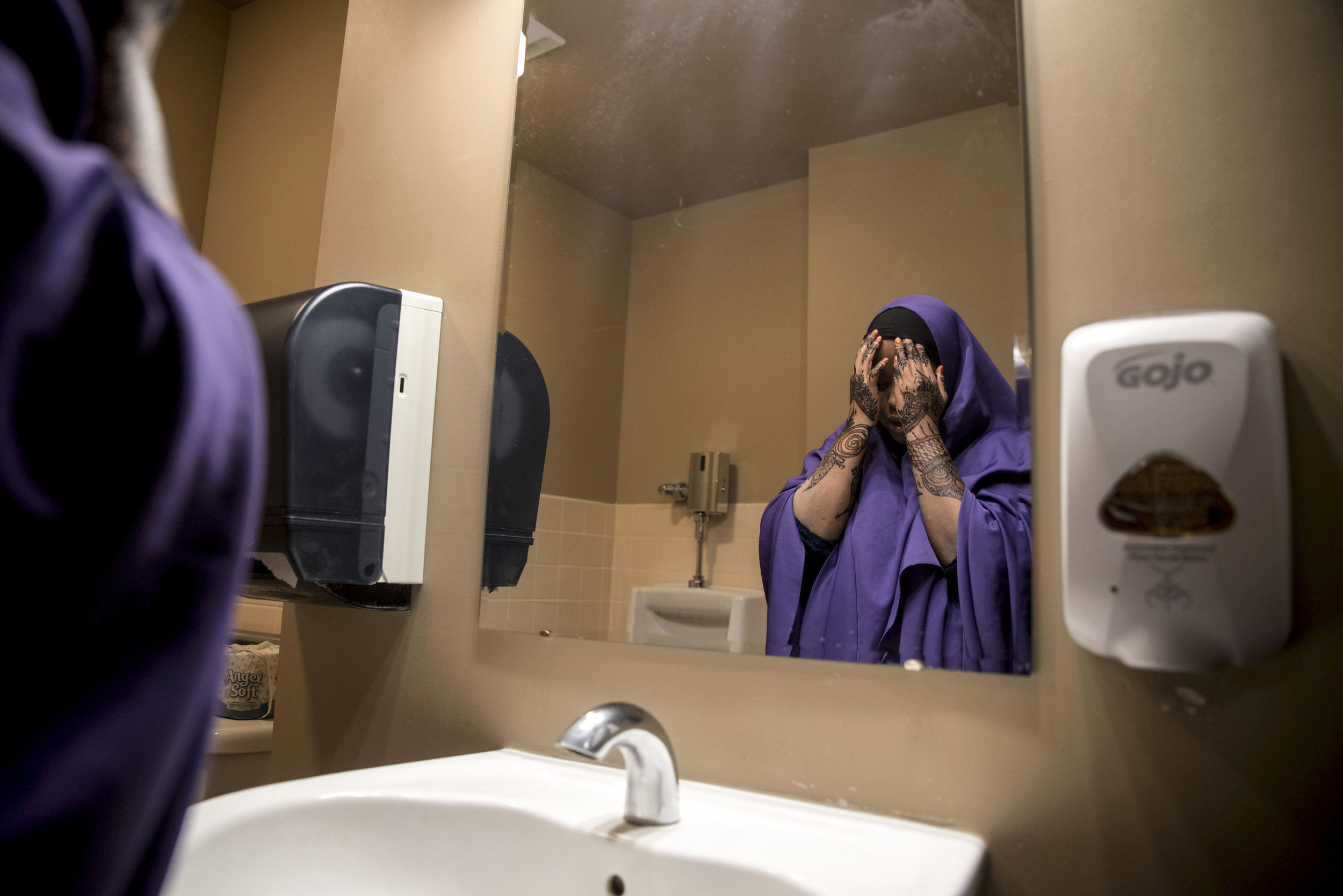 """Kosar washes her face in the bathroom before praying during her lunch break at United Community Action Partnership Feb. 13 in Willmar. After graduating high school, she worked several jobs and now works as a Somali Bilingual Outreach Worker at UCAP. As a Muslim, Kosar prays five times a day. """"Being able to pray at work makes my life so much easier,"""" Kosar said. """"I've had many jobs where I wasn't able to pray because of discrimination or because I wasn't able to take my break at a certain time."""""""