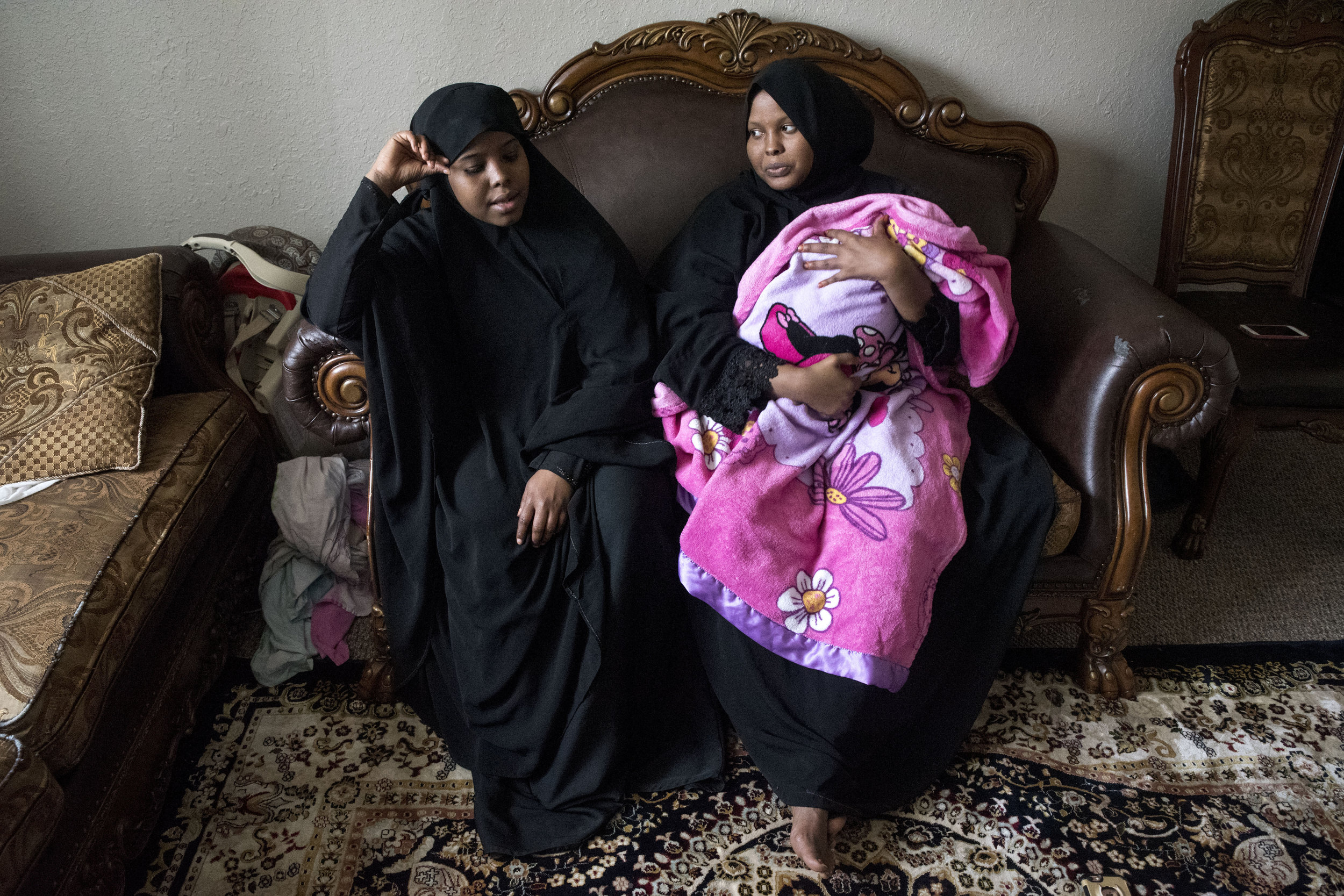 """Hamdi Kosar, left, and her sister Ismahan Kosar with her three-month-old son Ilhan Liban sit on the couch in their apartment in Willmar Mar. 30. Kosar's sister gave birth to Liban this January. Both sisters stayed in Minnesota while their family lives in Kenya for several years. """"I am going to miss them, but I have a life here now,"""" said Kosar. """"It was hard to see them go but, I've created a community here and I want to keep working."""""""
