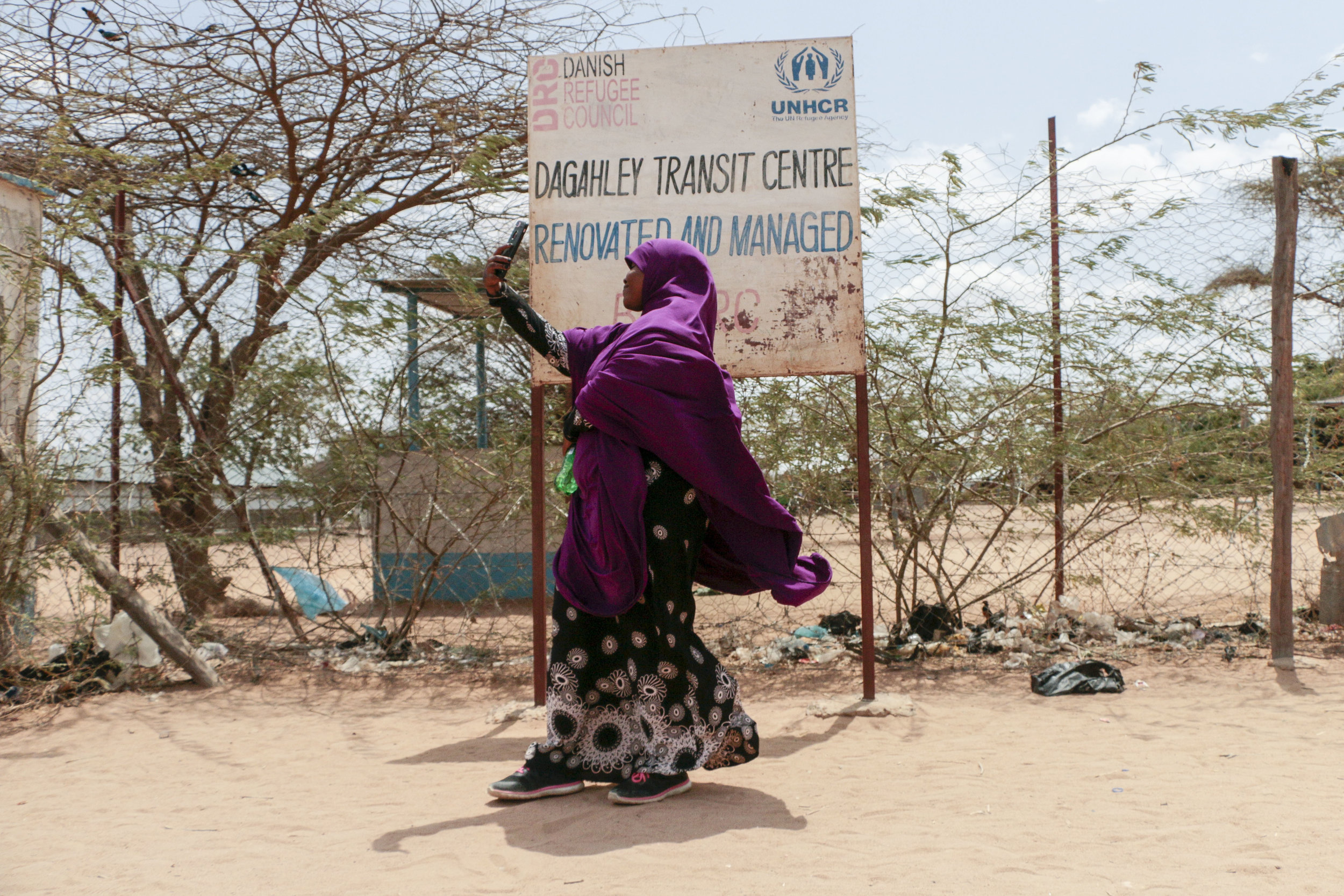 Hamdi Kosar takes a selfie with her phone in front of the Dagahaley Transit Centre sign Aug. 19, 2019 at the Dagahaley Refugee Camp in Dadaab, Kenya. Kosar, 21, was born at the refugee camp and lived there throughout most of her pre-teen years. This is the first time she has been back to the camp in almost a decade.
