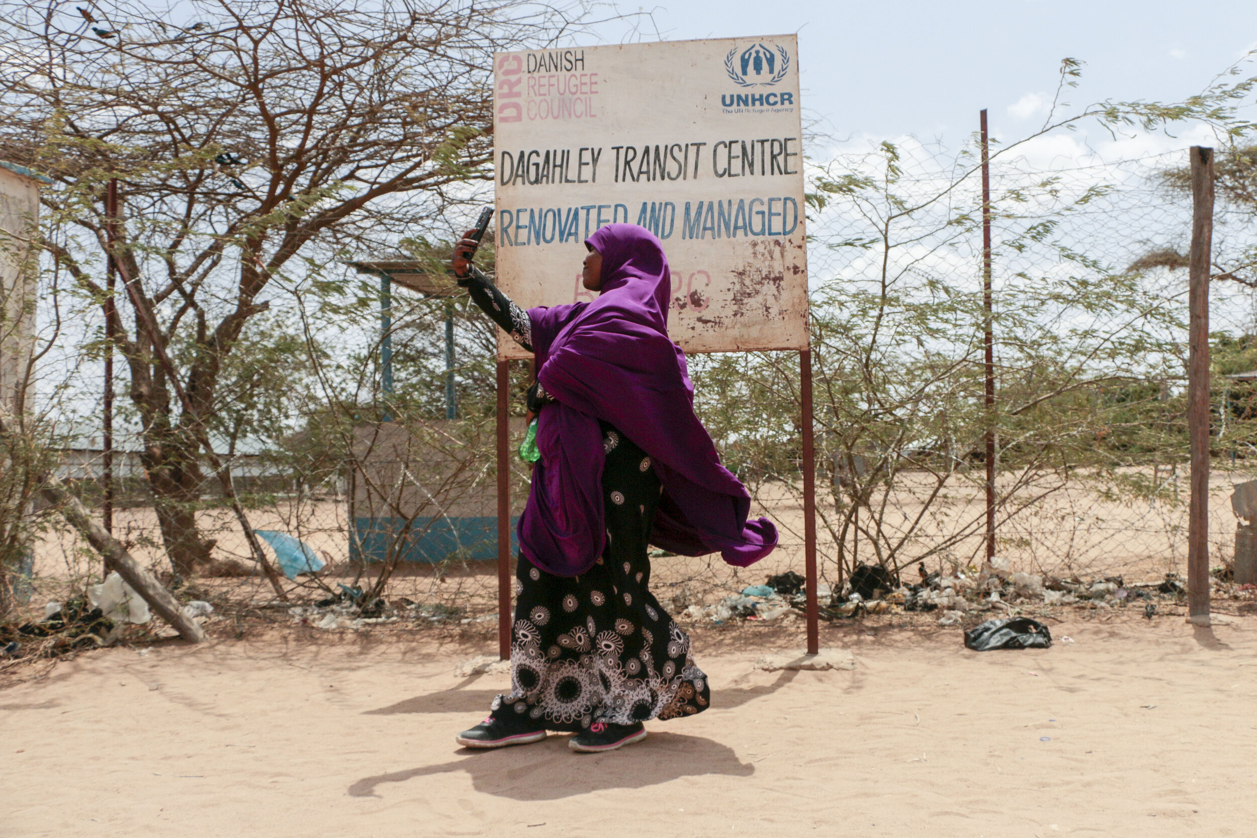 Hamdi Kosar takes a selfie with her phone in front of the Dagahaley Transit Centre sign Aug. 19 at the Dagahaley Refugee Camp in Dadaab, Kenya. Kosar, 21, was born at the refugee camp and lived there throughout most of her pre-teen years. This is the first time she has been back to the camp in almost a decade.