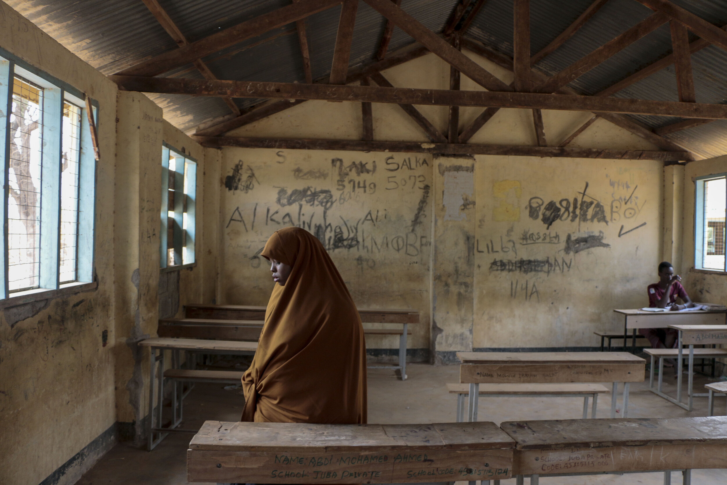 Hamdi Kosar stands up after sitting at a desk in her former elementary school, Juba Primary School, Aug. 19 at the Dagahaley Refugee Camp in Dadaab, Kenya. The school offers many forms of enrichment, including the debate team which she was a part of during her time there. Kosar's father was also a school teacher and taught at Juba Primary School.