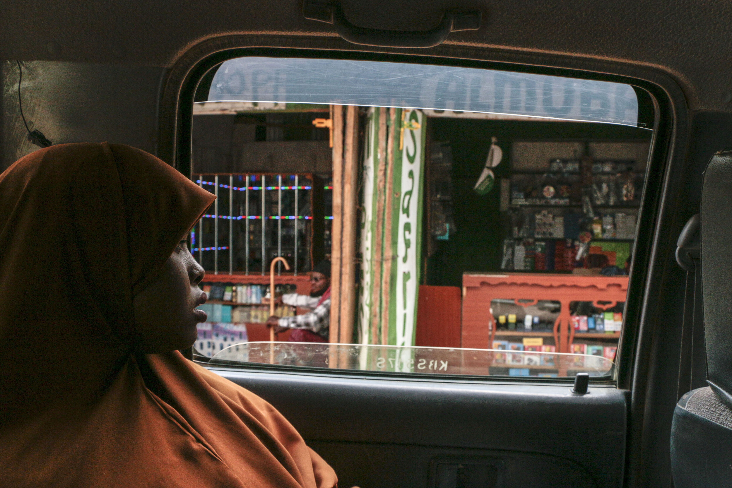 """Hamdi Kosar looks out the window while driving through the marketplace Aug. 19 at the Dagahaley Refugee Camp in Dadaab, Kenya. Many refugees have their own business and sell goods at the market place within the camp. """"It brings back memories,"""" Kosar said."""