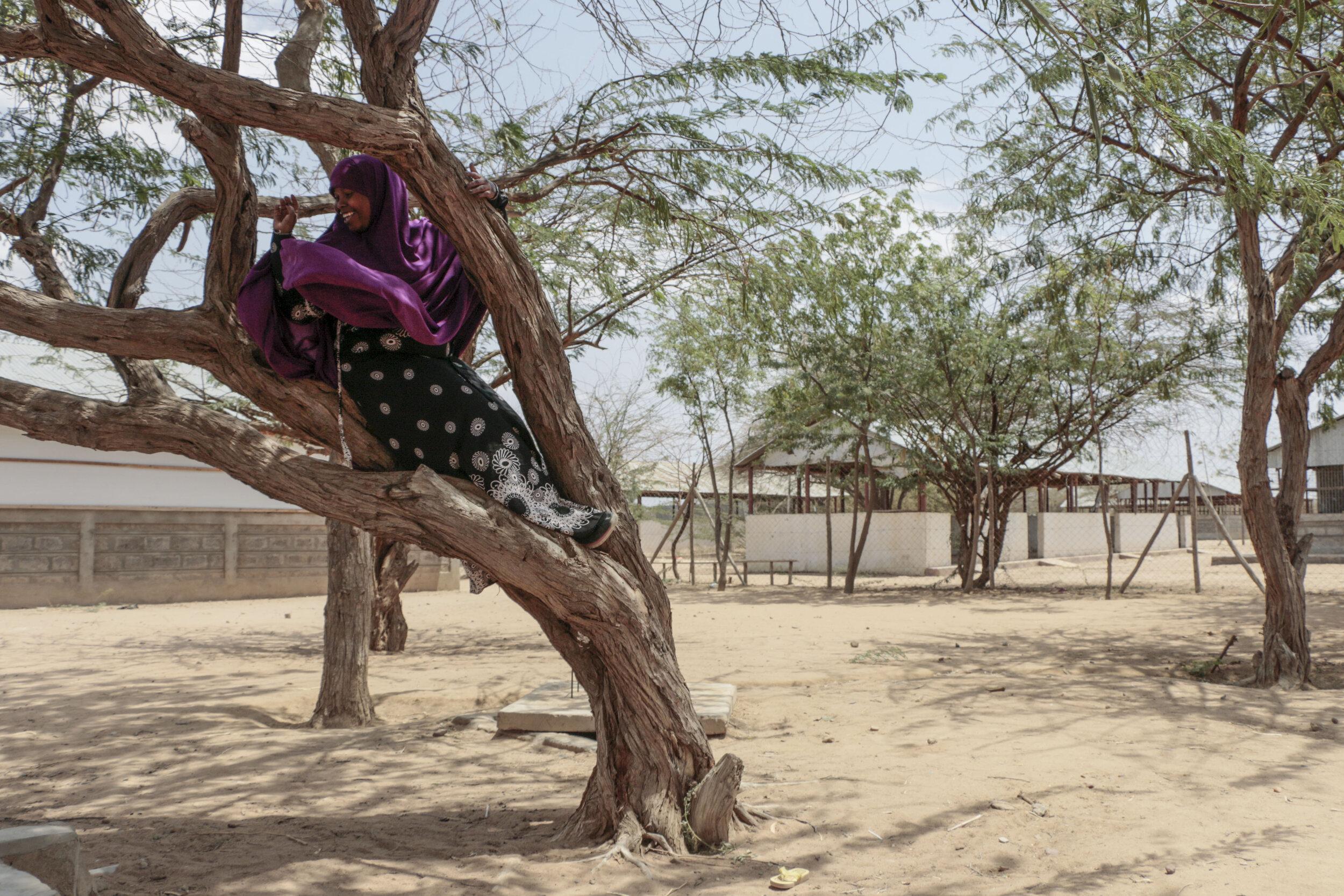 "Hamdi Kosar climbs a tree ""just like I used to do"" Aug. 19 at the Dagahaley Refugee Camp in Dadaab, Kenya."