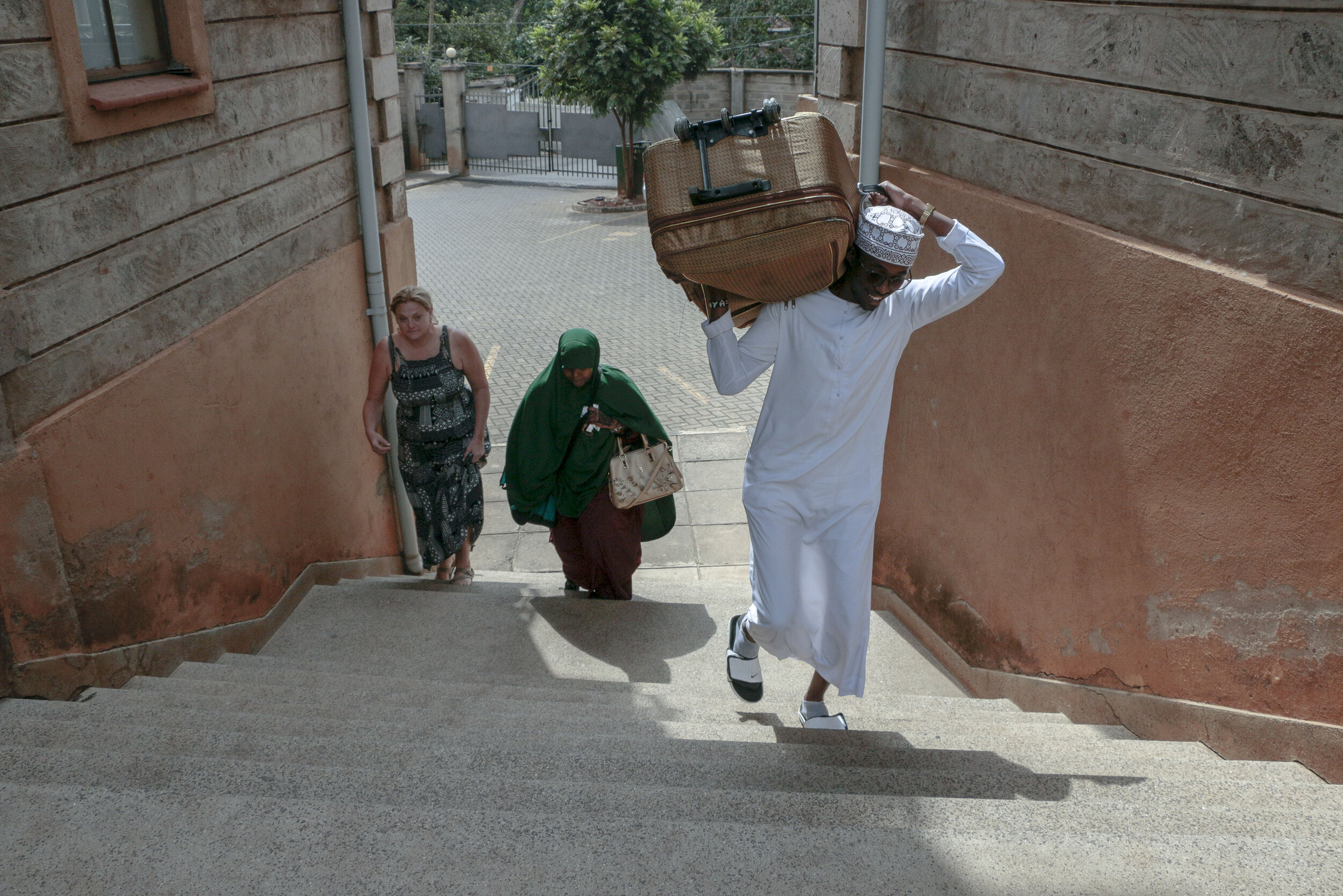 Khalid Ahmed, Kosar's cousin, helps lift a suitcase up the steps while Hamdi Kosar and Jessica Rohloff follow Aug. 23 in Nairobi. Kosar had met Ahmed just several days before and has many family members that she has never met after being resettled to the U.S.