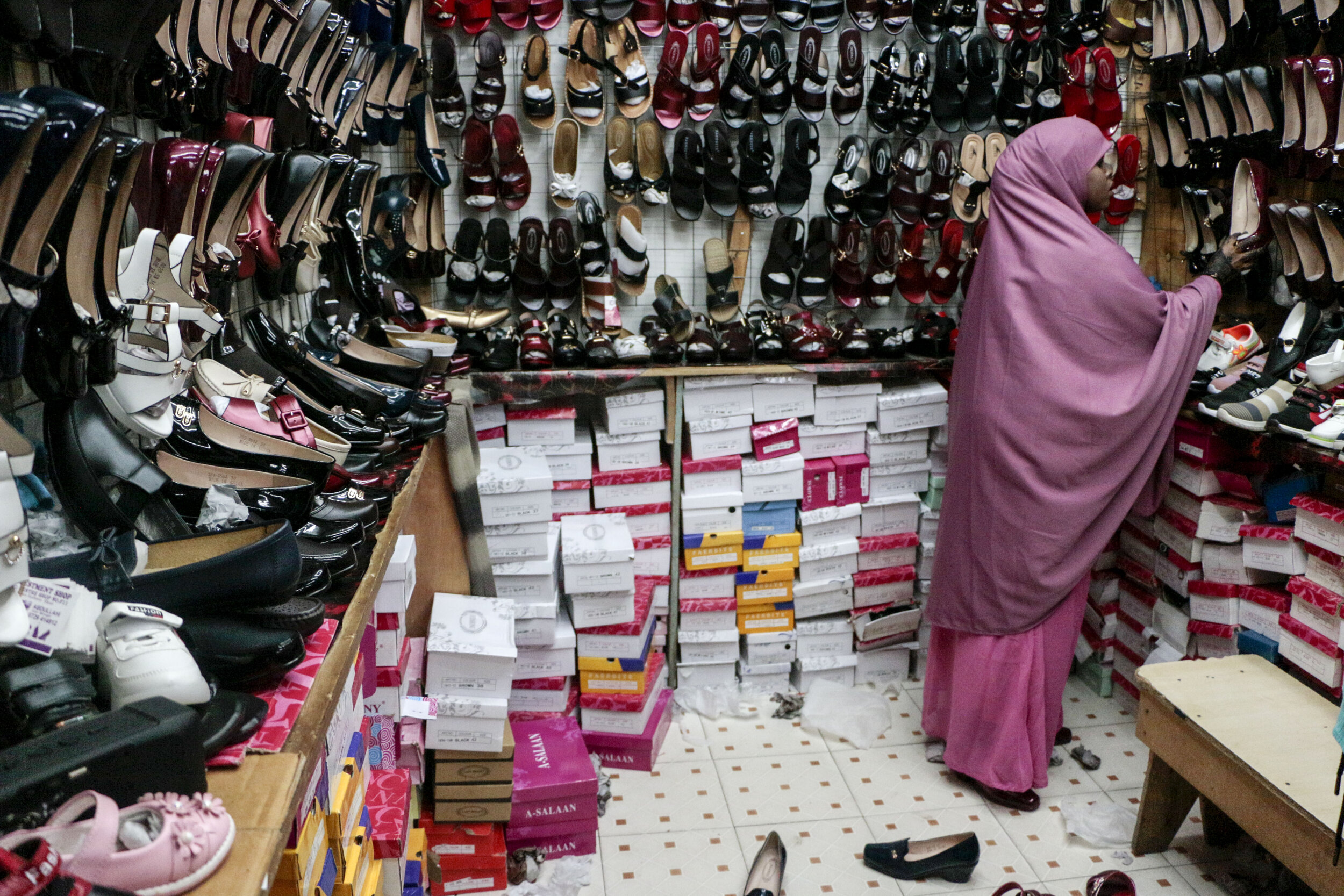 Hamdi Kosar looks at shoes at a market in the Eastleigh neighborhood Aug. 16 in Nairobi. The neighborhood is predominantly inhabited by Somali Muslims and many refugees shop here while they are in the resettlement centers before they head elsewhere to seek asylum.