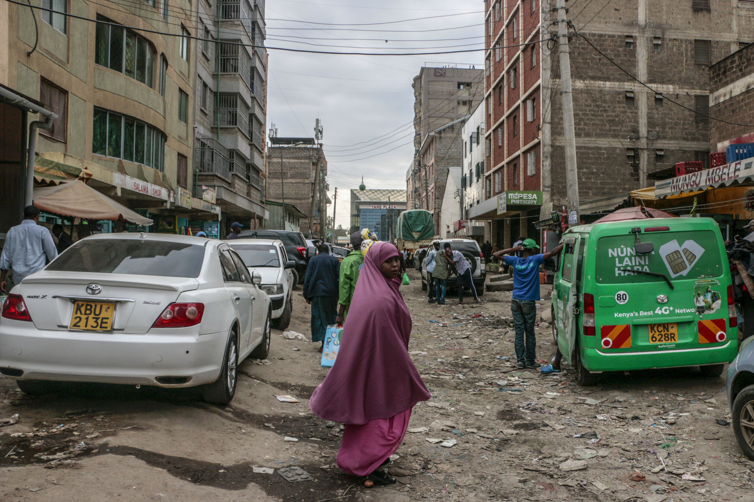 """Hamdi Kosar pauses while walking through the streets of Eastleigh, a predominantly Muslim and Somali neighborhood in Nairobi, Aug. 16. Many Somali refugees shop here while they are in the resettlement centers before they head elsewhere to seek asylum. This neighborhood was particularly hard for Kosar to see. """"It's very emotional for me to see this,"""" she said. """"My religion teaches us to care for the poor and people don't even stop to talk to them. I want to help people, but I also feel helpless because I can't give them enough."""
