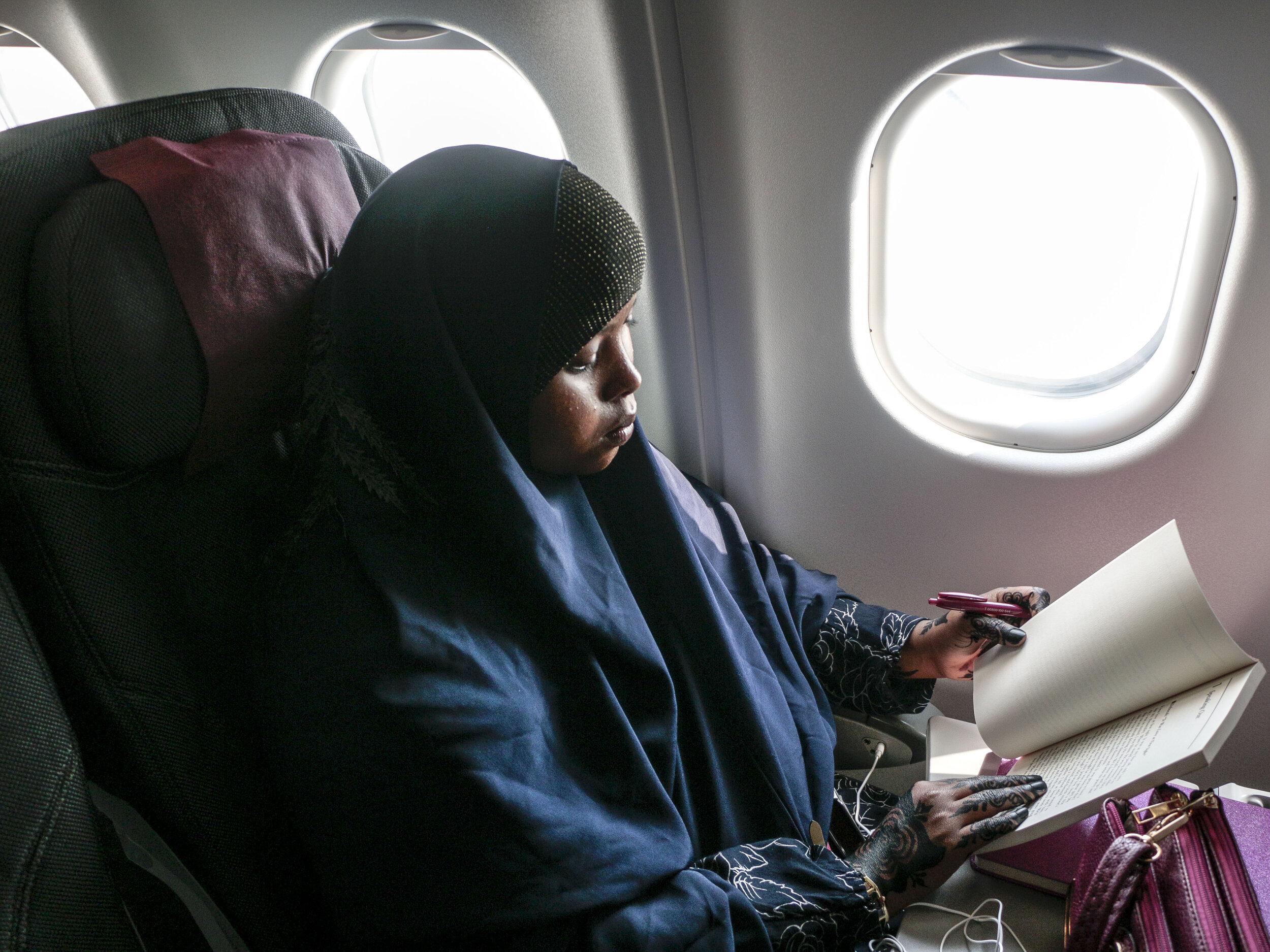 "Hamdi Kosar reads on the flight from Doha, Qatar to Nairobi, Kenya Aug. 14 at the Hamad International Airport. ""I'm really excited and it'll bring back a lot of memories,"" Kosar said about returning to Kenya."
