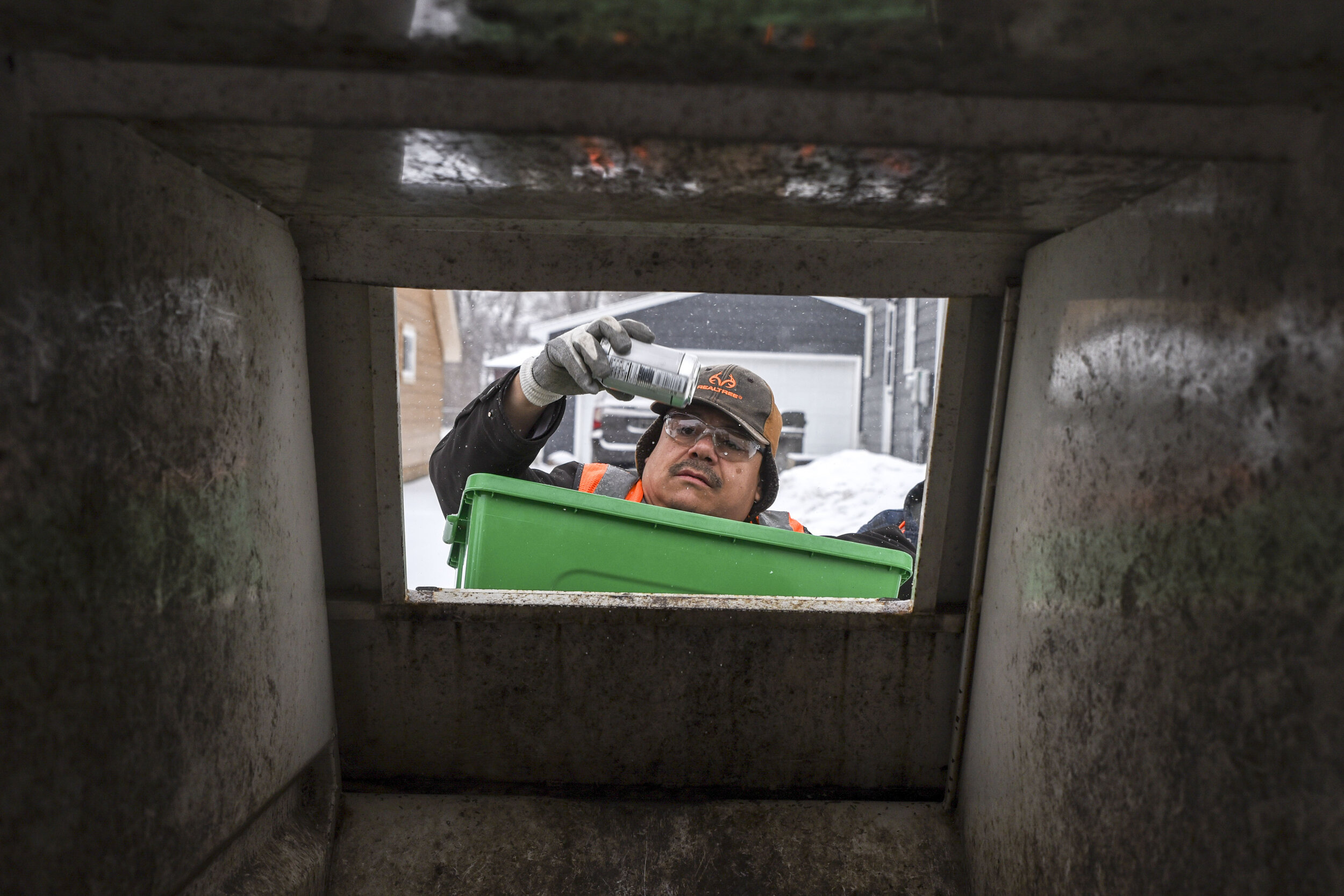 Elijah Gomez puts a can in the recycling pickup truck during his volunteer hours Mar. 20 in Willmar.