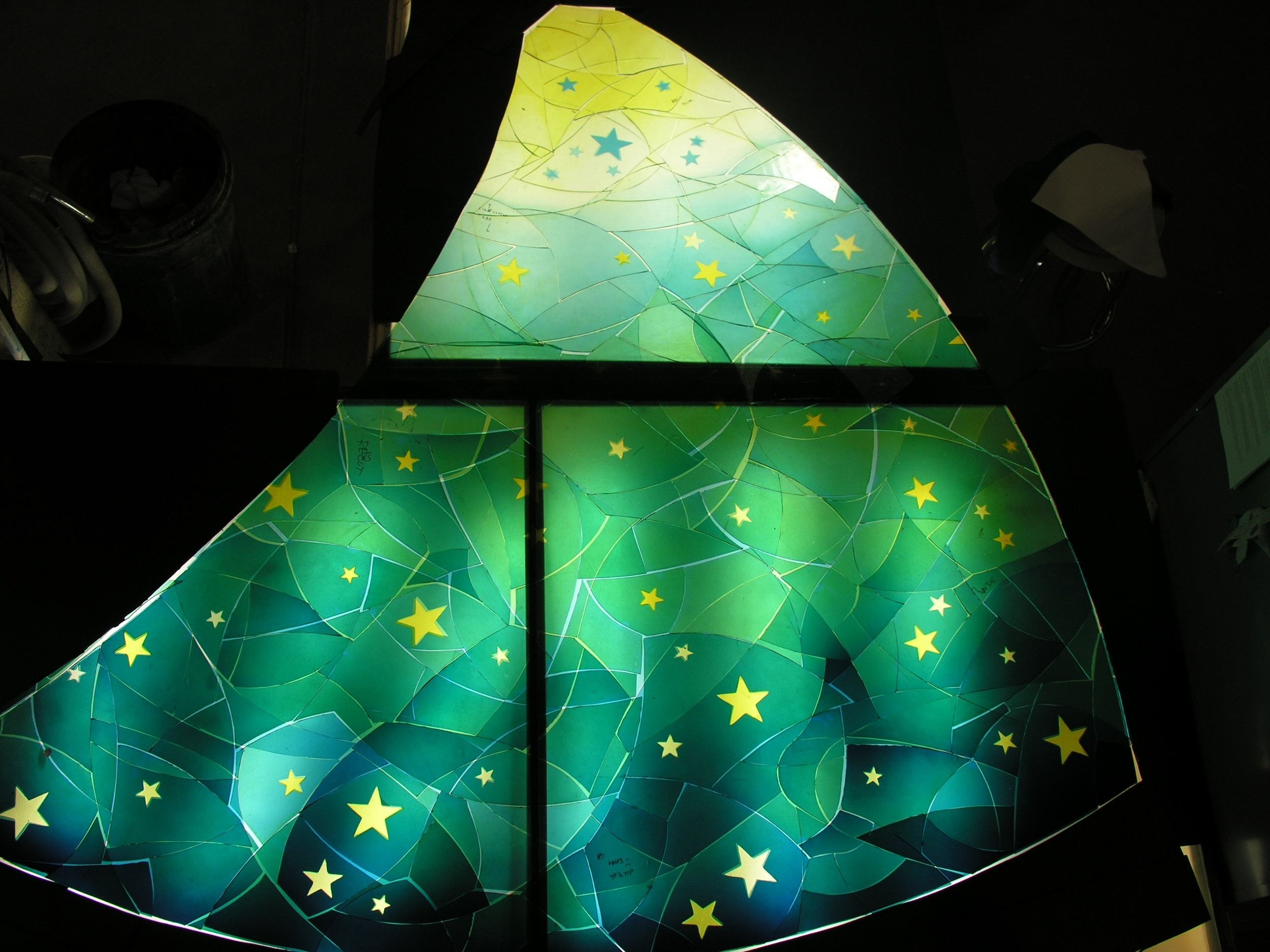 The stars are now etched out and pieces laid out on a table.  The is the finished Silver Stain, which you can see by the distinctive transparent yellow on top of the blue glass.
