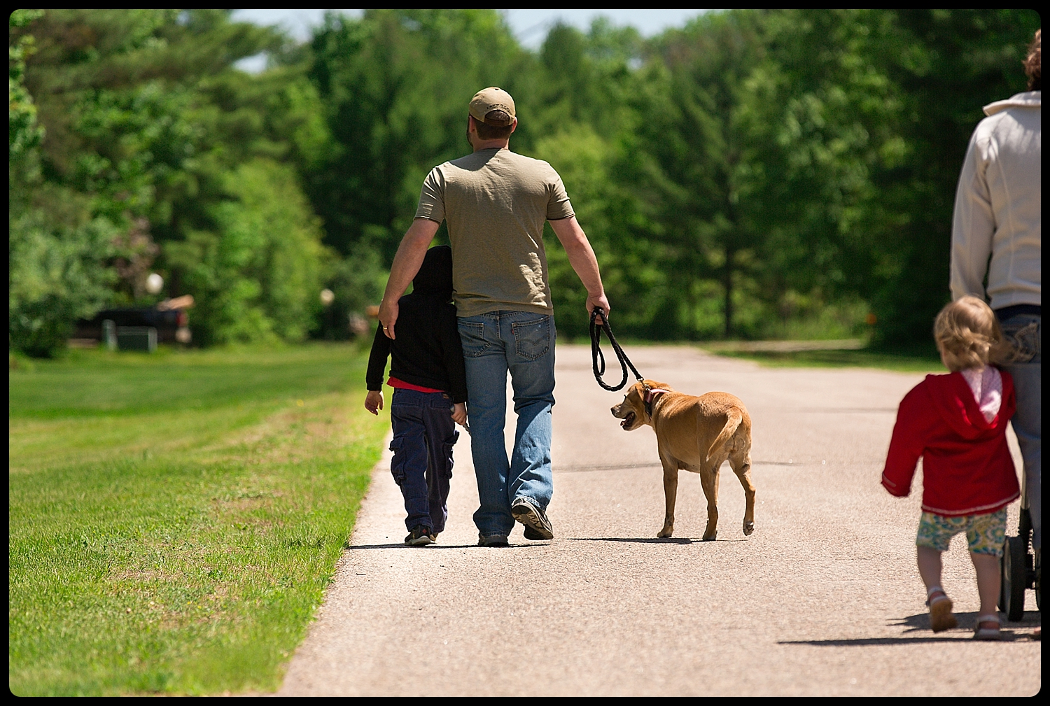 Family goes for a walk while dad snuggles son and walks dog.