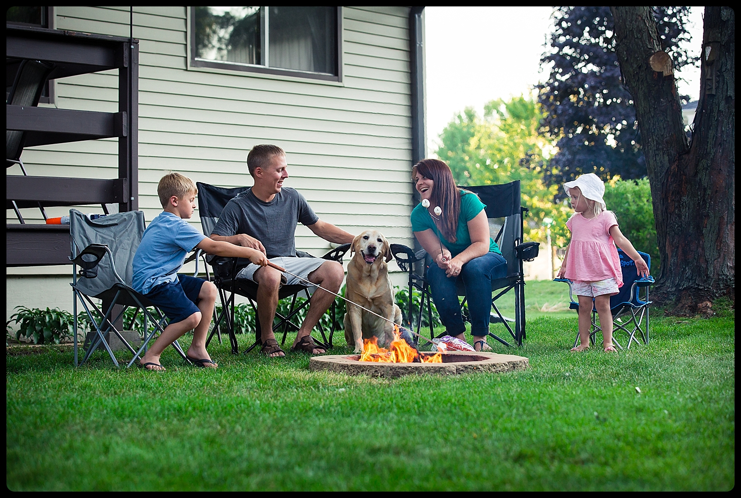 Family has campfire as dog smiles at camera.
