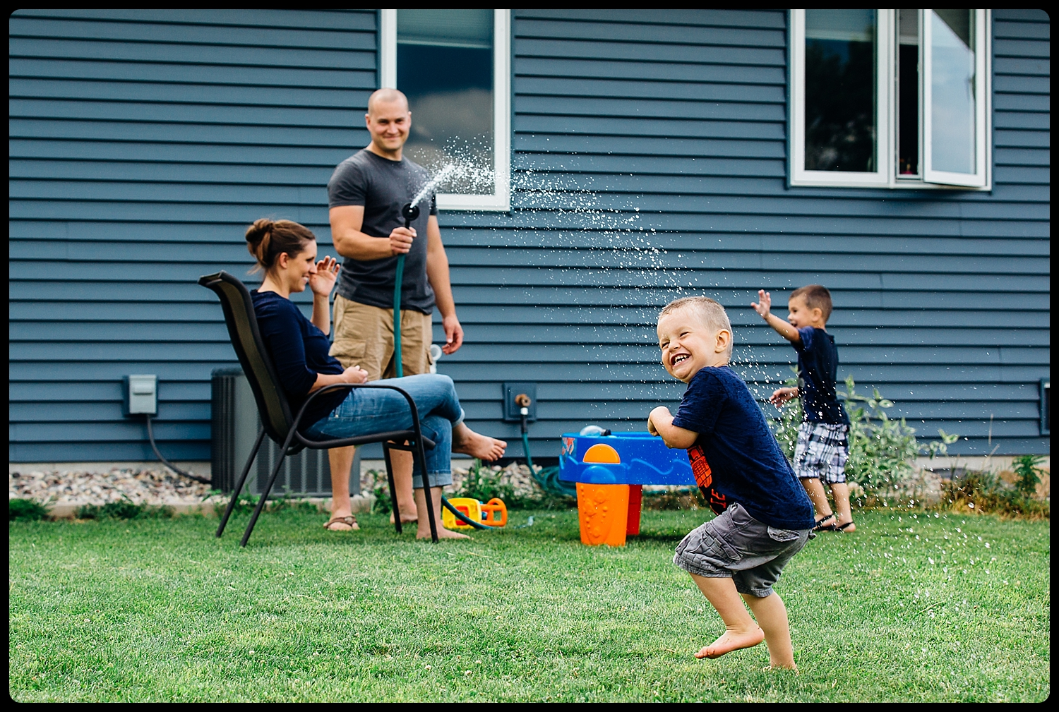 Dad squirts son with hose outside.