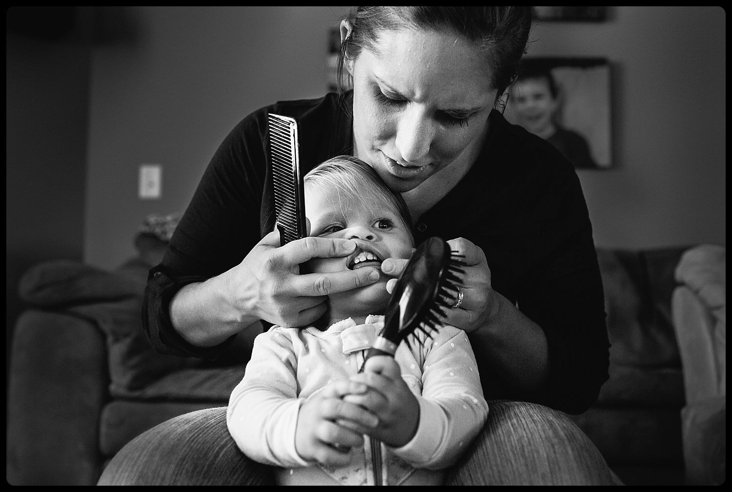 Mom pulls hair out of toddler's mouth after toddler puts brush in mouth.