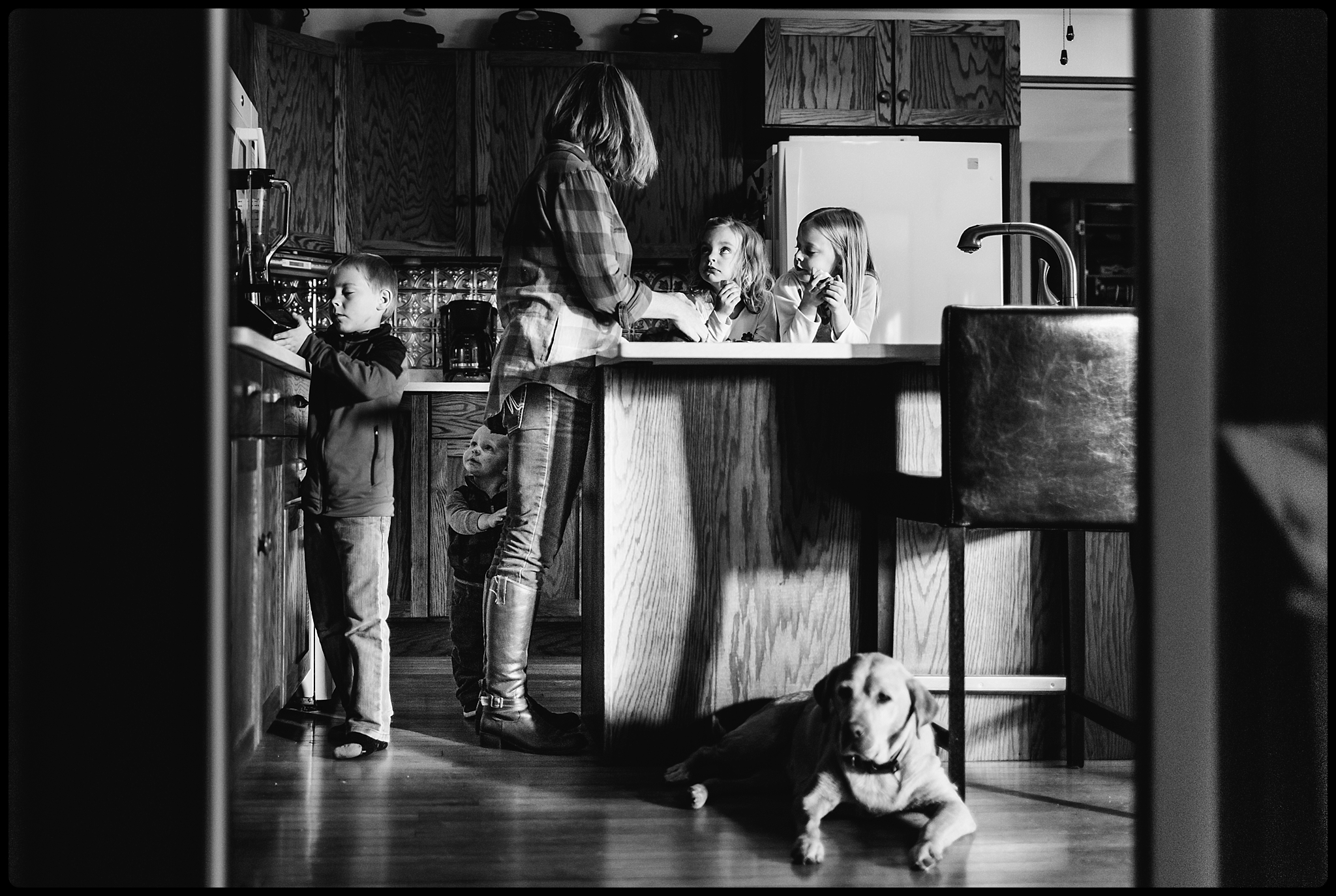 Family hangs out together in kitchen.