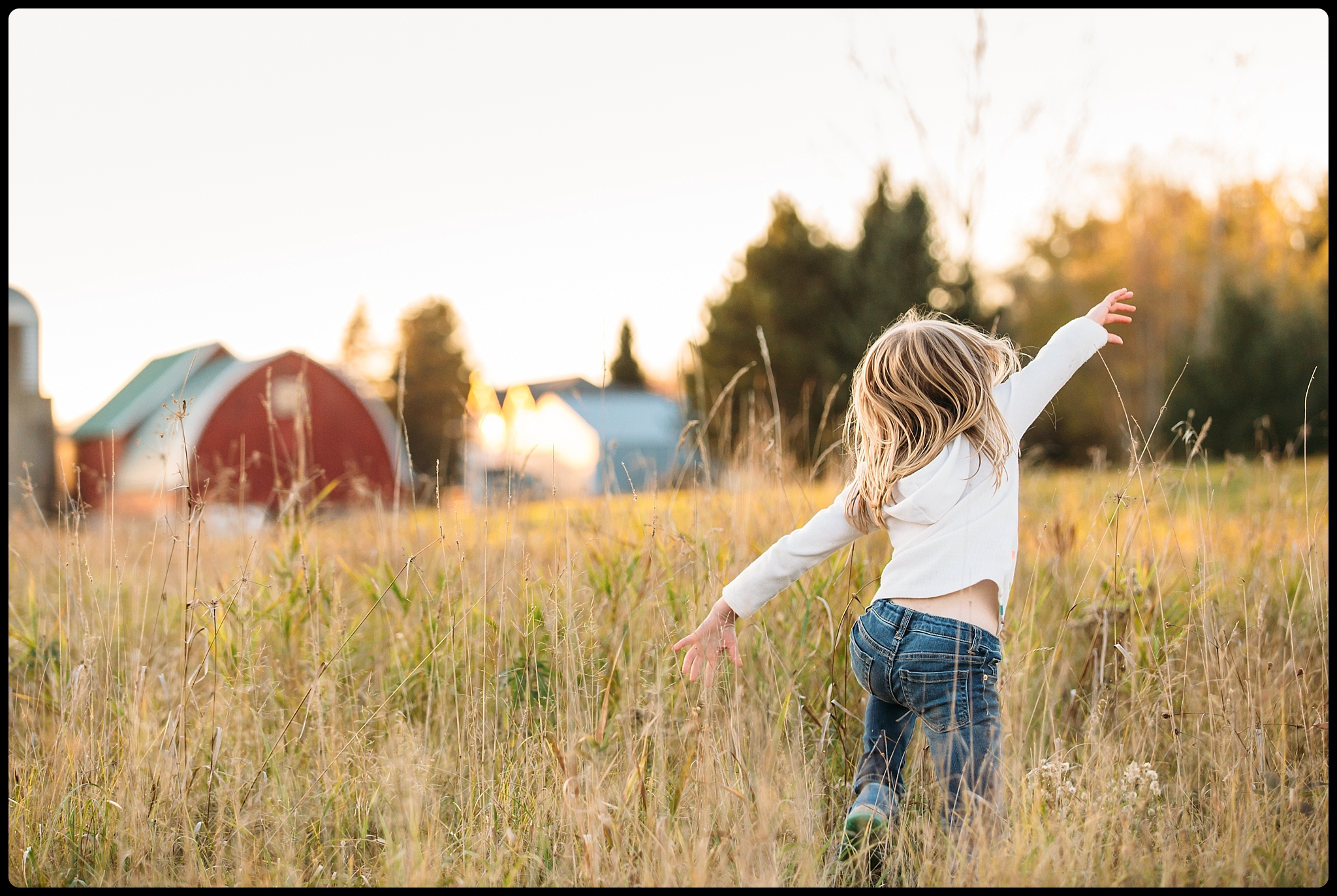Girl playing in a field near a barn.