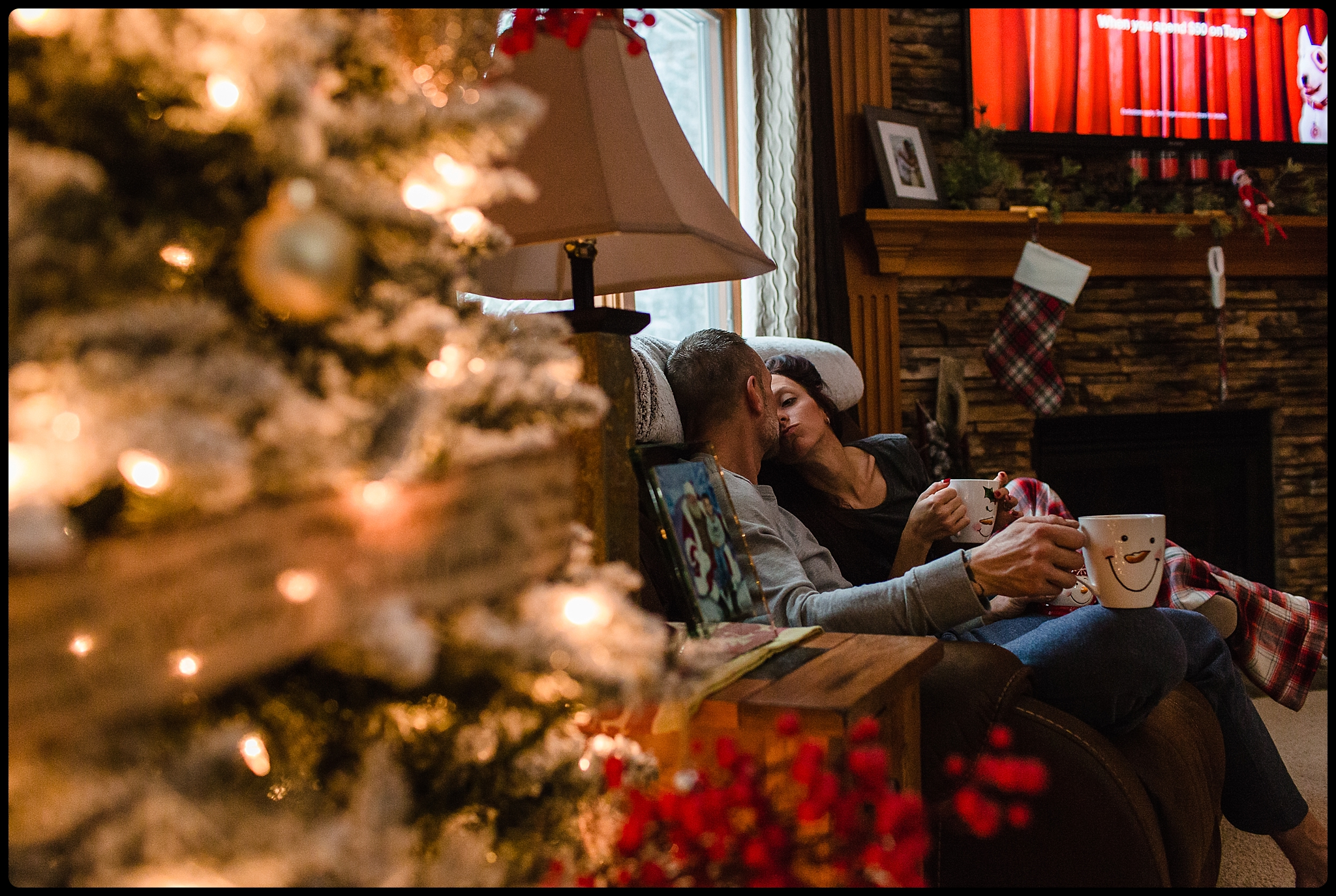Couple shares a kiss over hot cocoa at Christmas time.