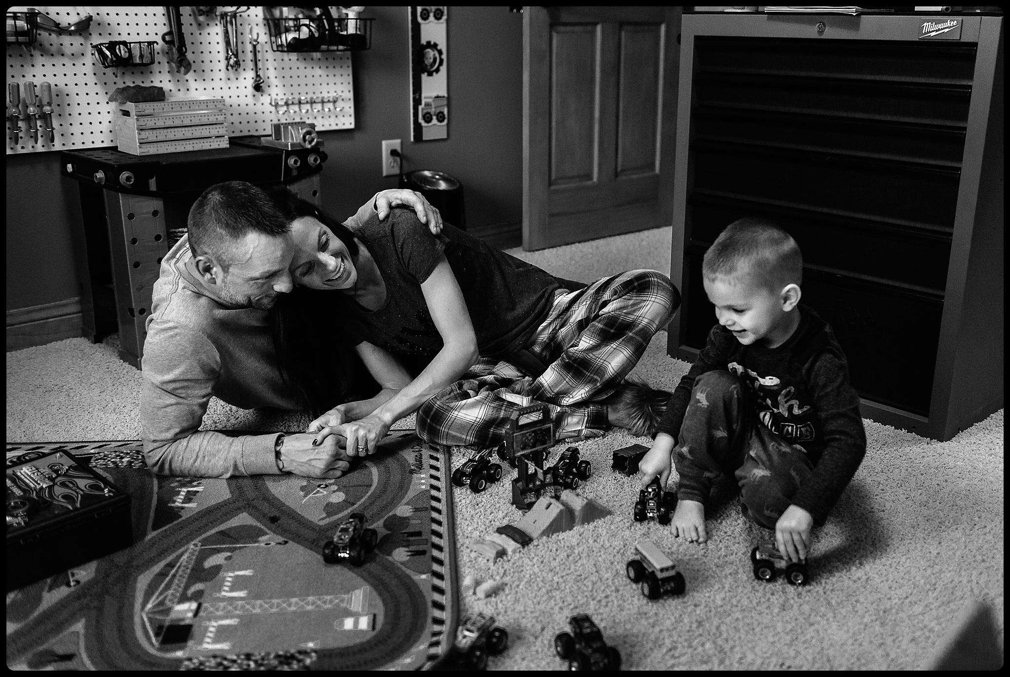 Family playing with cars in a boy's bedroom.