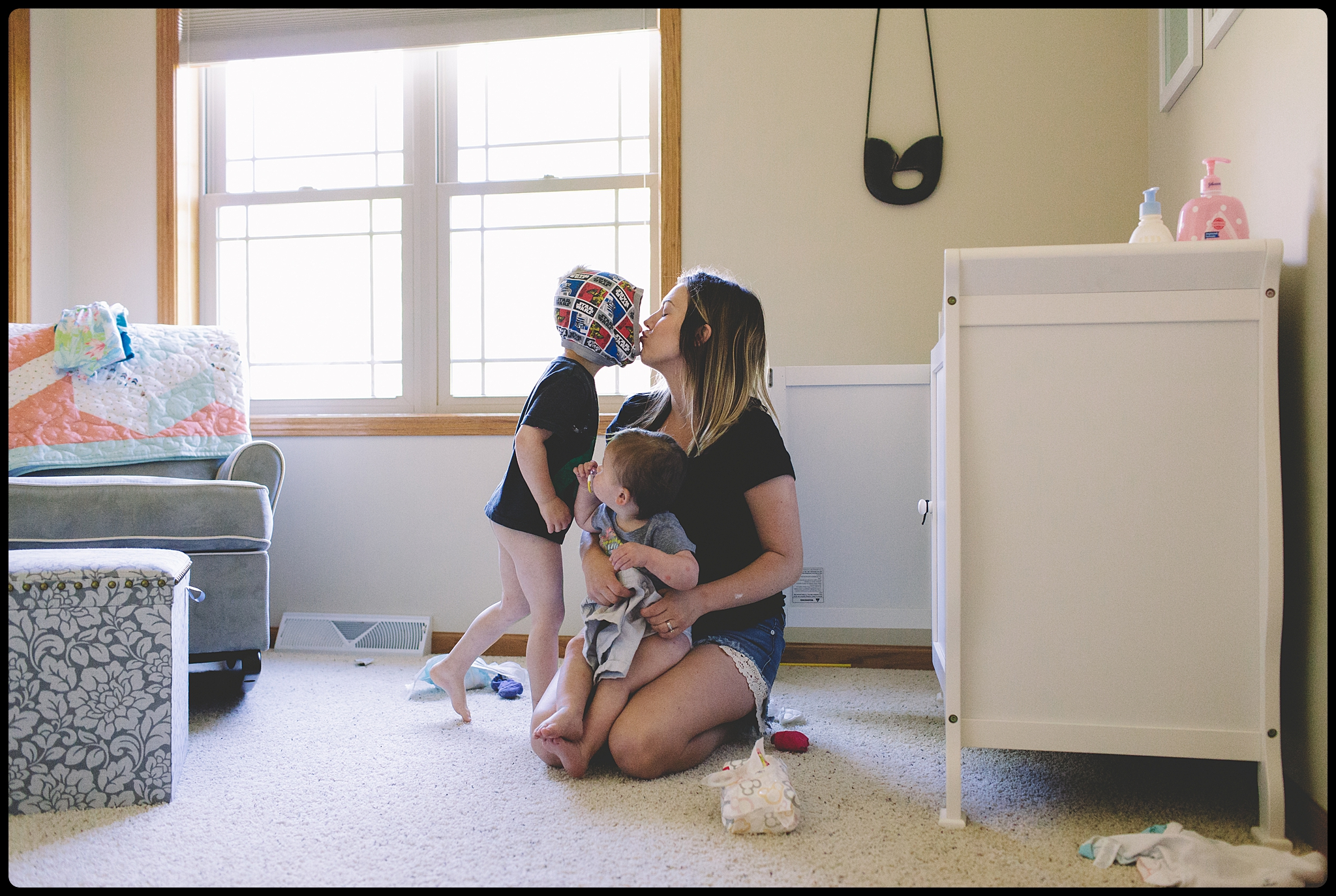 Boy with underwear on his head, kisses mom who's changing baby diaper.