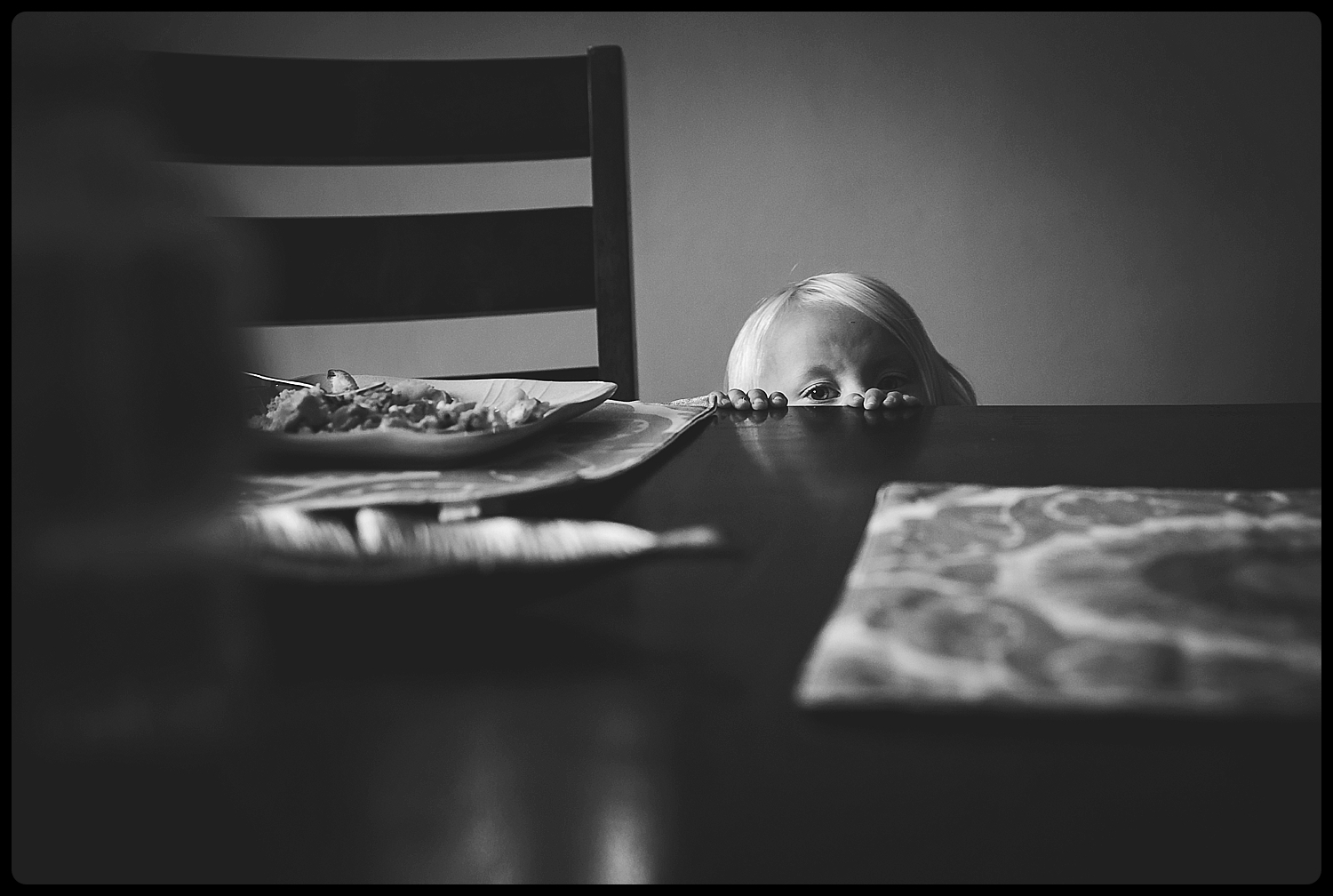 Little girl peeking up over kitchen table.