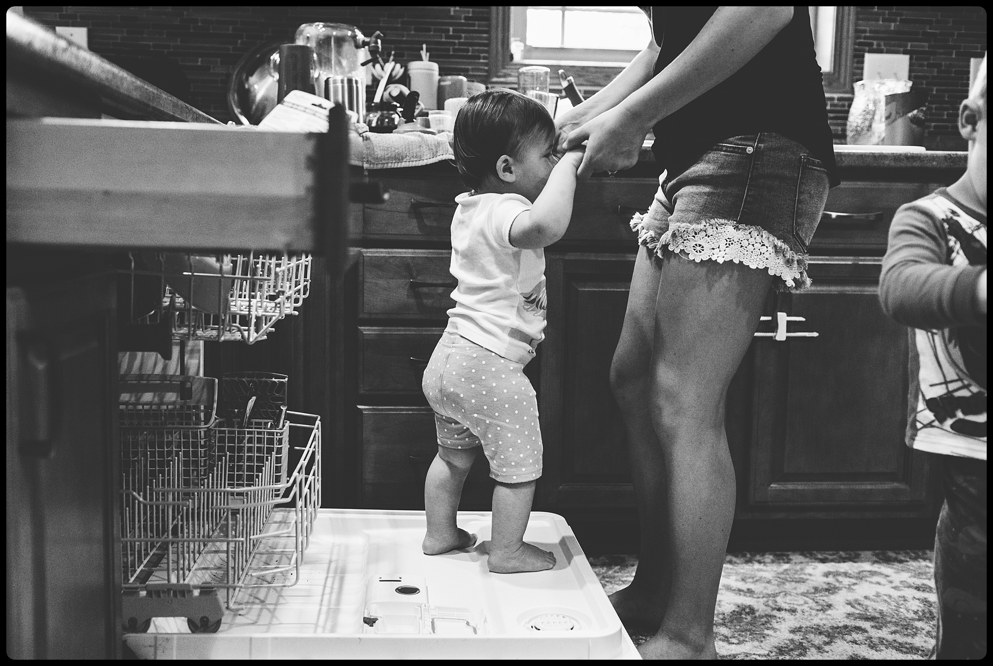 Baby climbs on dishwasher while mom is trying to clean.