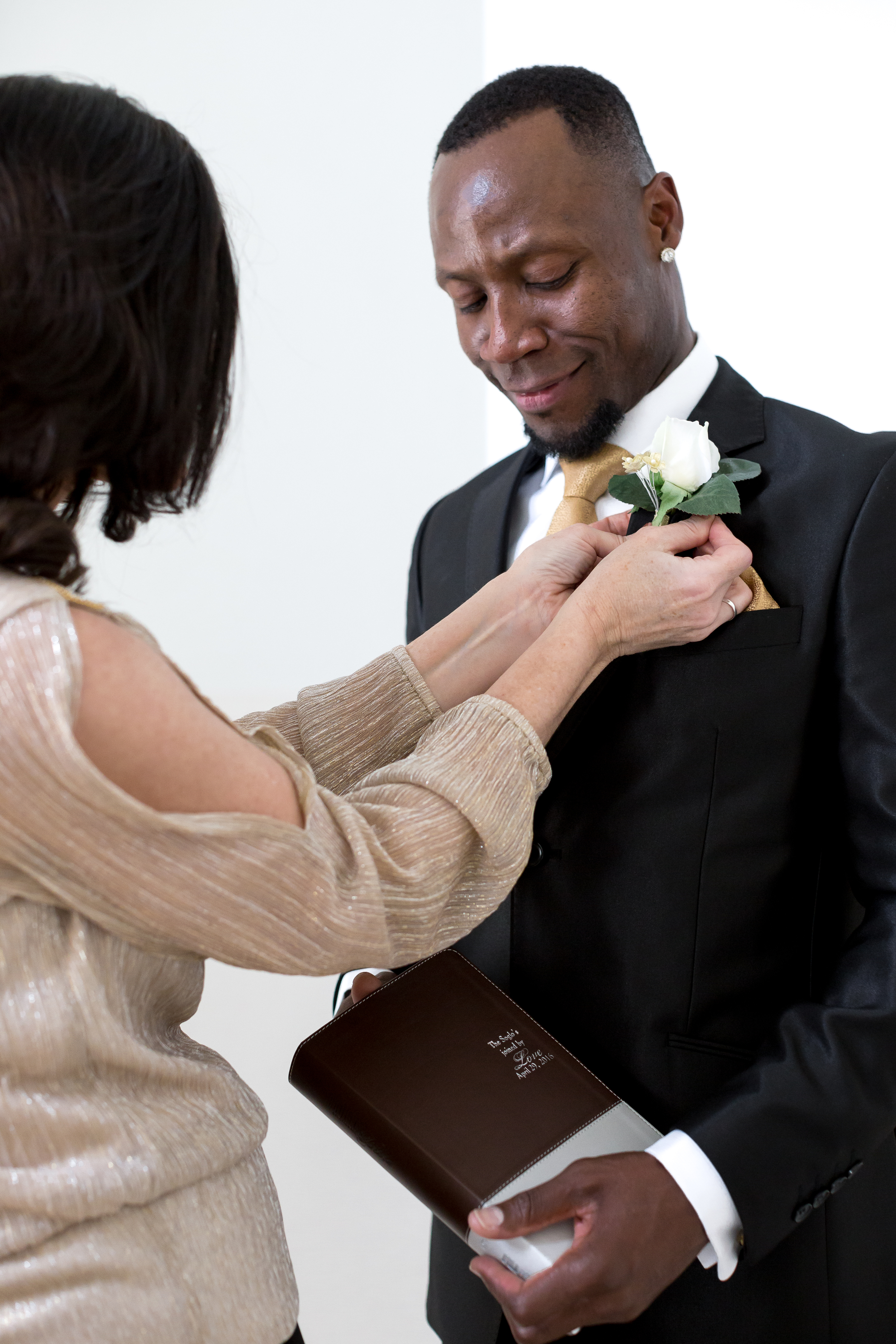 Melissa gave him a Bible as their wedding gift.Here her mother pins on his boutineer.