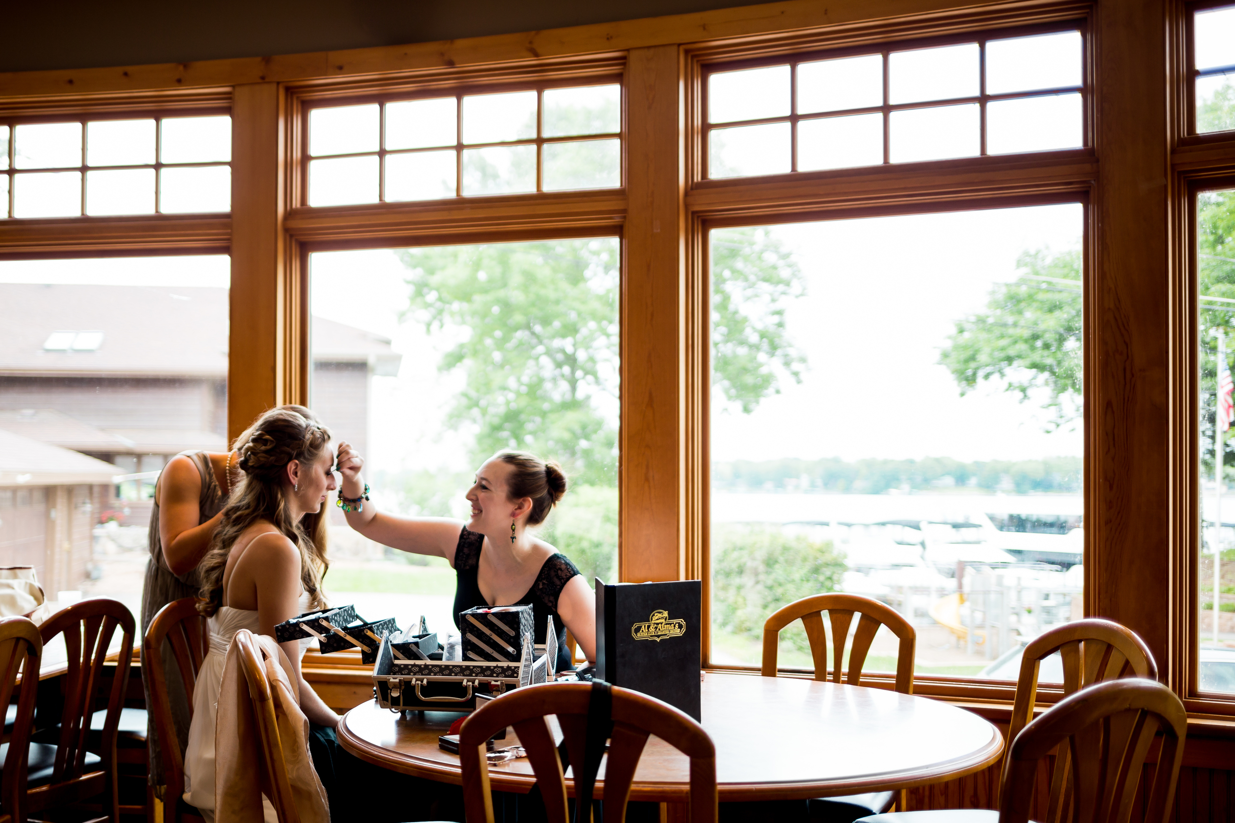 Our bride Robin sits near the window light as her sister Josie does her makeup.