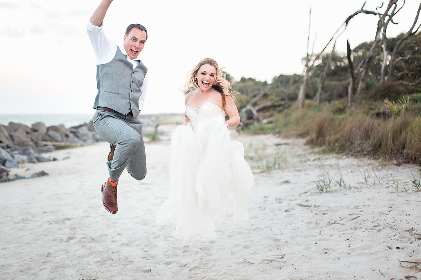 Bride and groom jumping in Driftwood beach after their wedding ceremony.