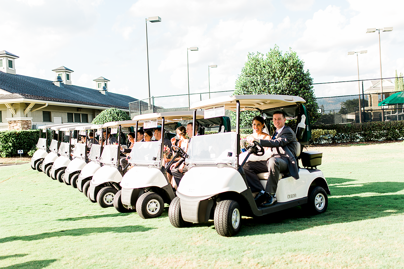 newblyweds and the whole bridal party driving golf carts