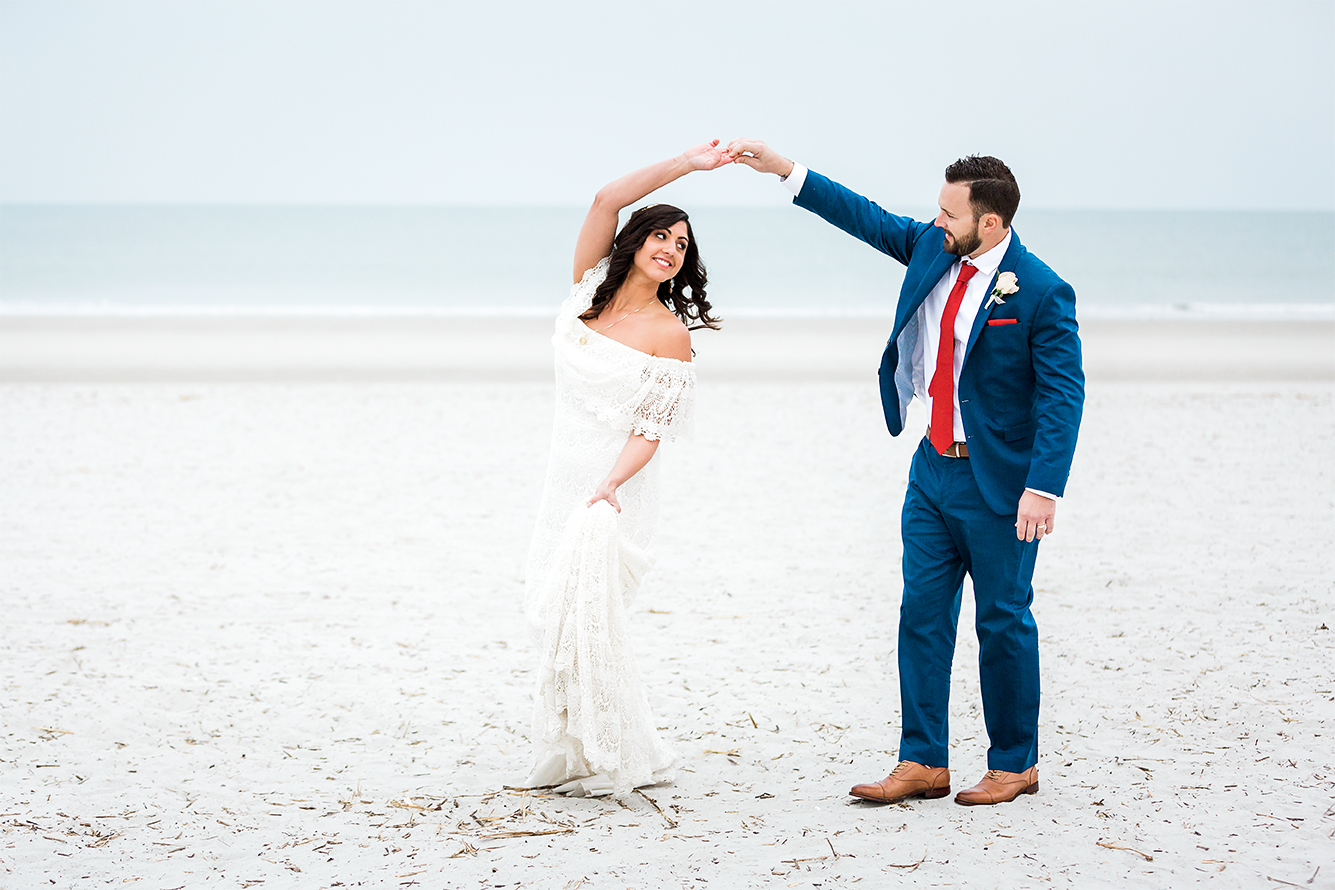 bride and groom dancing in the beach after the wedding